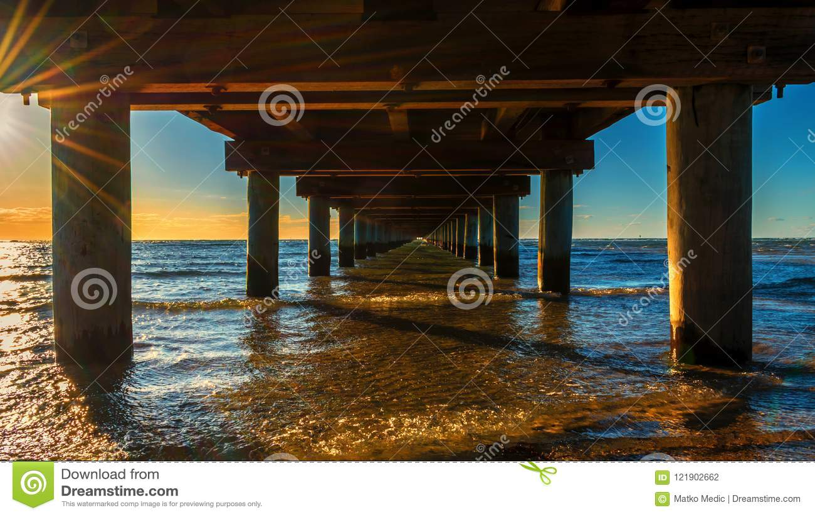 Under the pier at beautiful golden orange sunset