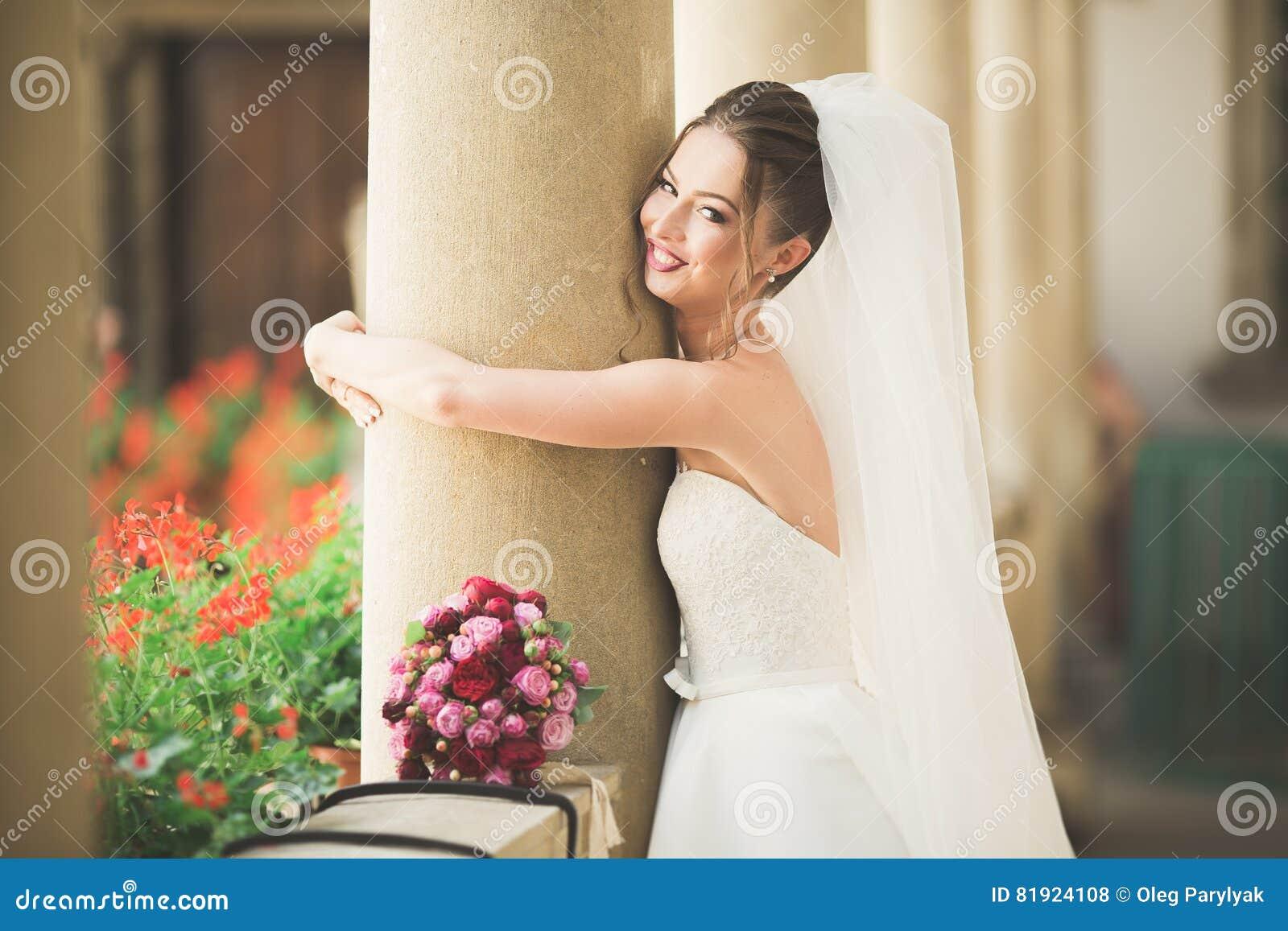 Underbar brud med en lyxig vit klänning som poserar i den gamla staden