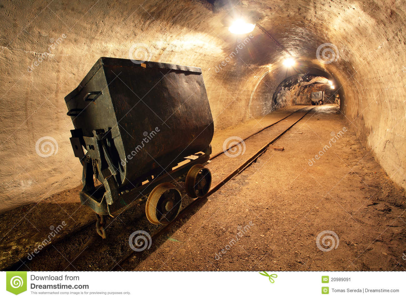 Underground train in mine, carts in gold, silver