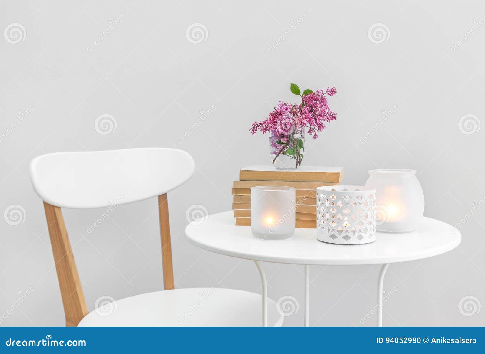 Undersöka ljus, böcker och blommor på en vit tabell