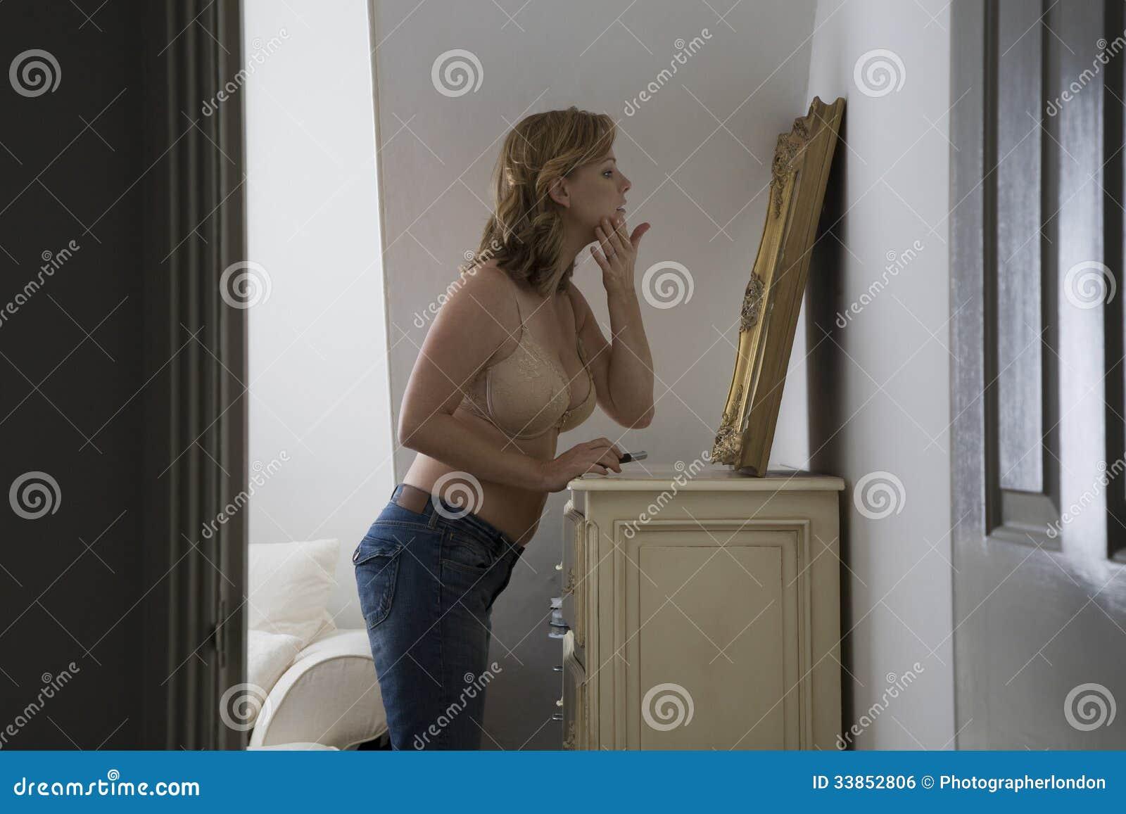 Undersökande framsida för halv klädd kvinna i spegel