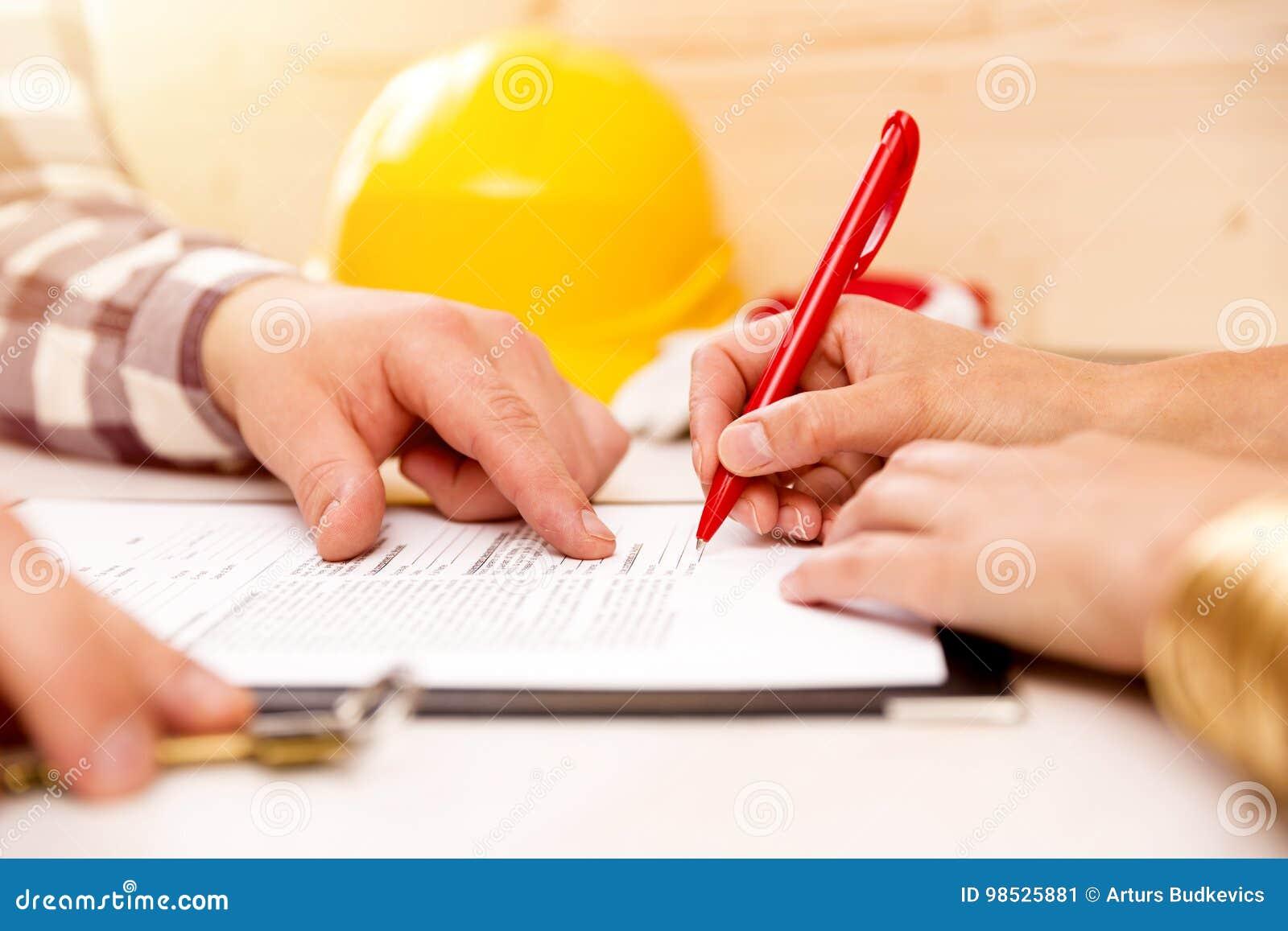 Undertecknande konstruktionsavtal för kvinna med leverantören som bygger ett hus