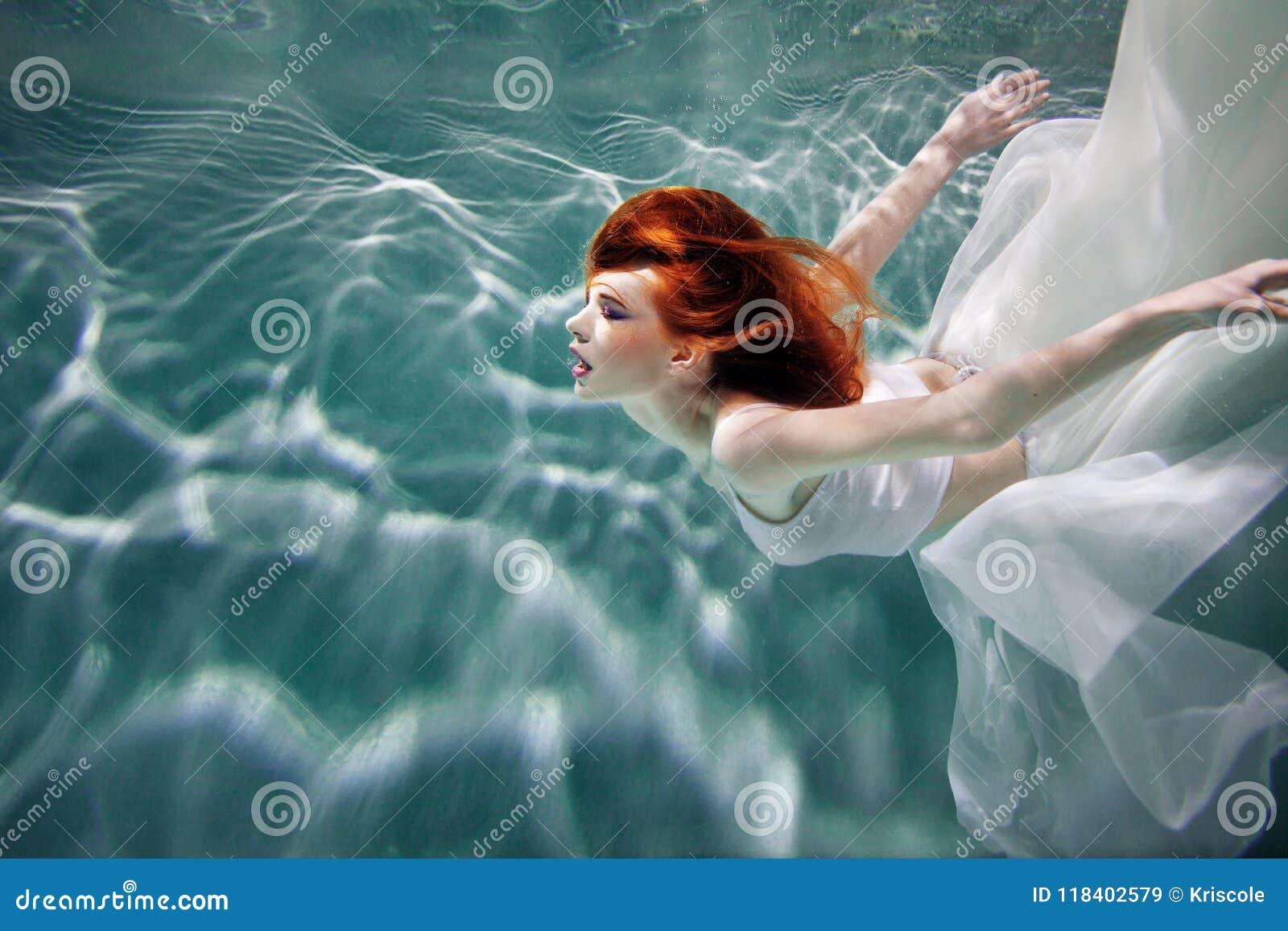 Undervattens- flicka Härlig rödhårig kvinna i en vit klänning som simmar under vatten