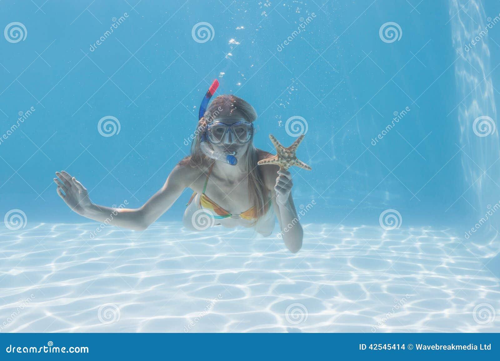 Underwater louro bonito na piscina com tubo de respiração e estrela do mar