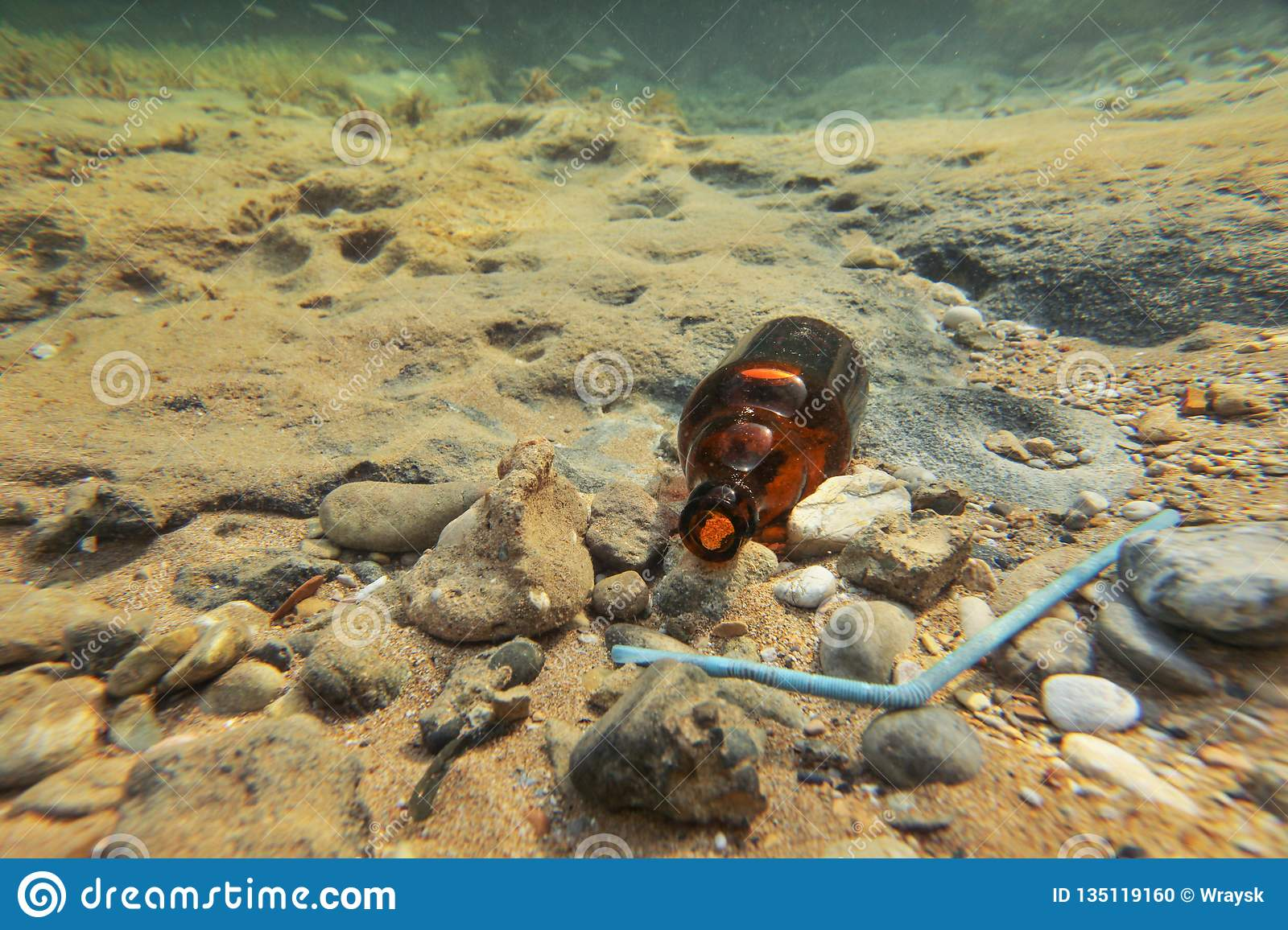 Underwater photo - small brown beer bottle and blue plastic straw on sea floor. Ocean littering concept
