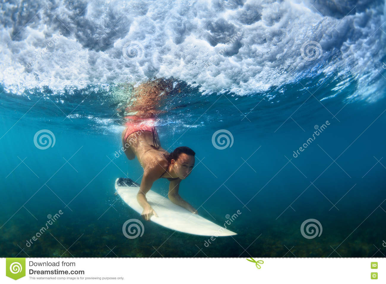 Underwater photo of surfer girl on surf board in ocean