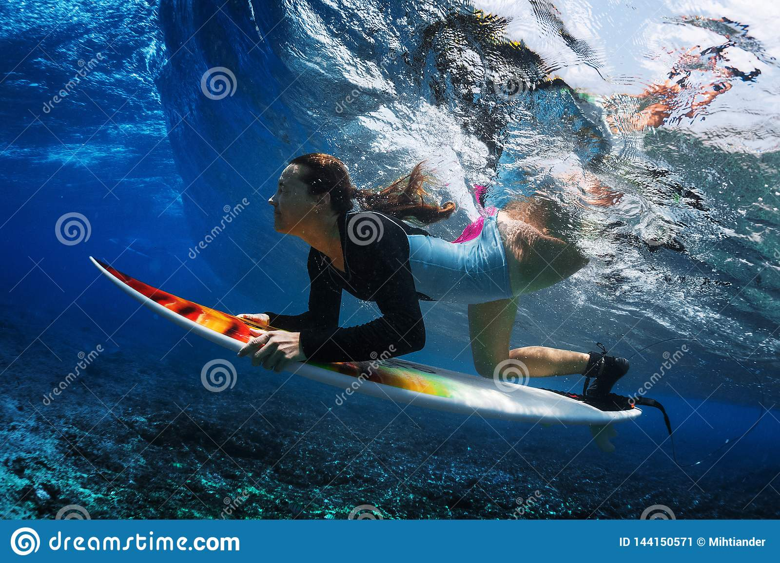 Underwater shot of the young woman surfer