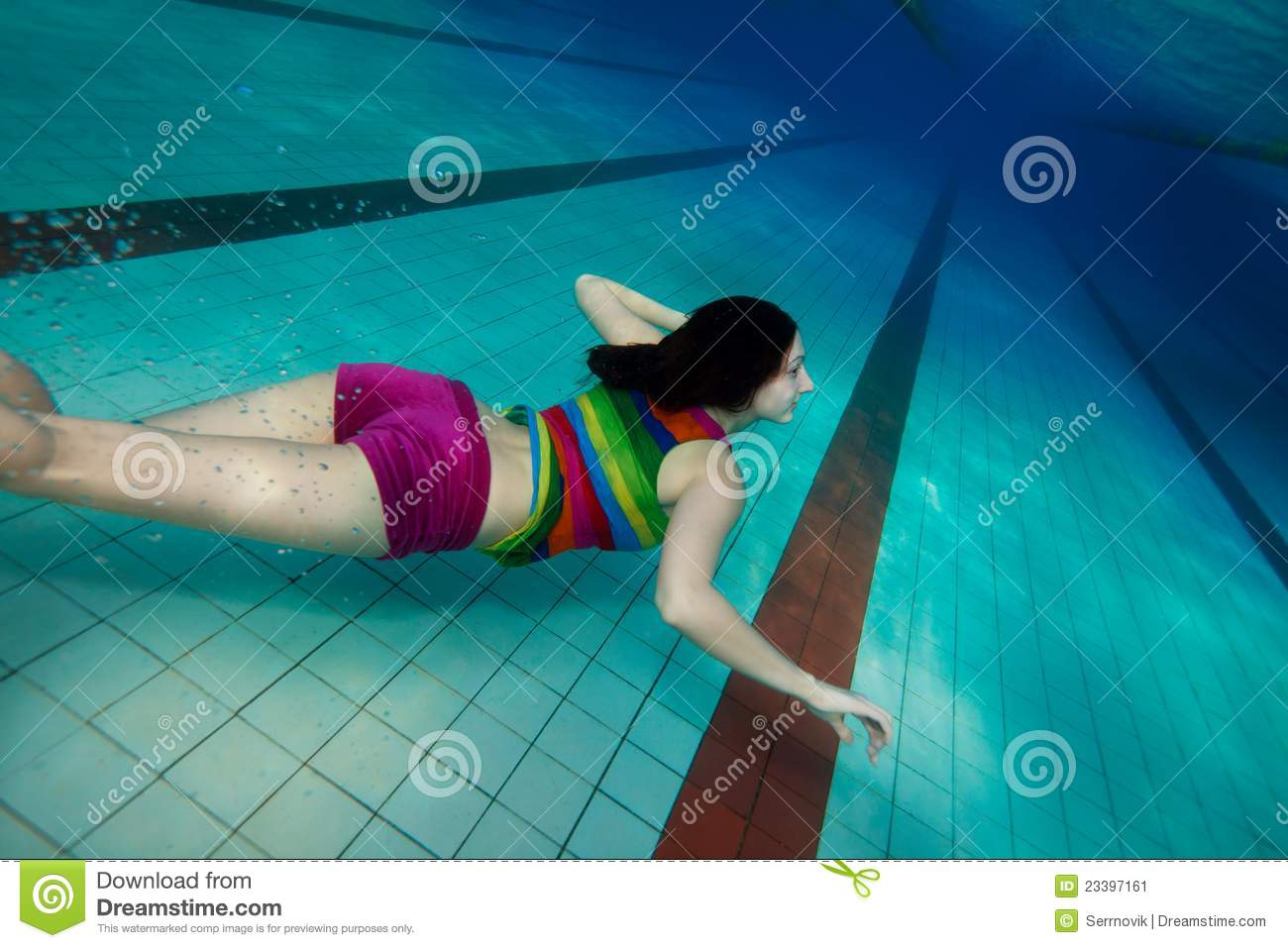 Happy girl in colorful clothes swimming underwater near the pool ...