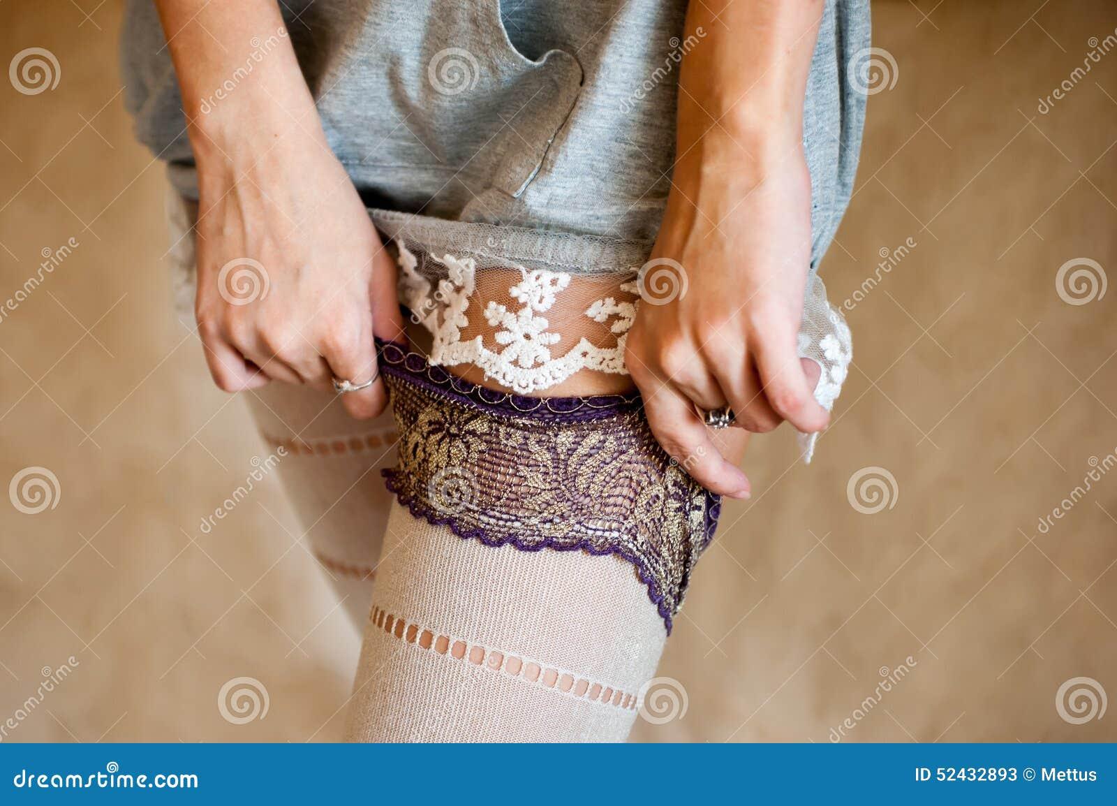 Одевает чулки, но трусов предусмотрительно не одевает