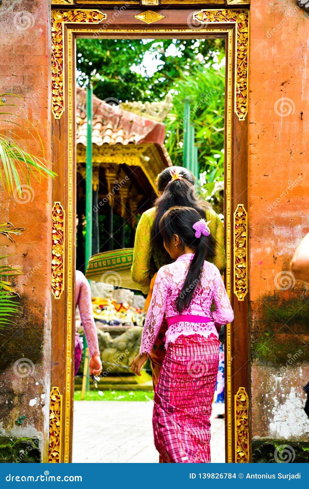 Une adolescente de Balinese portant l habillement local traditionnel entrant dans un temple sacré