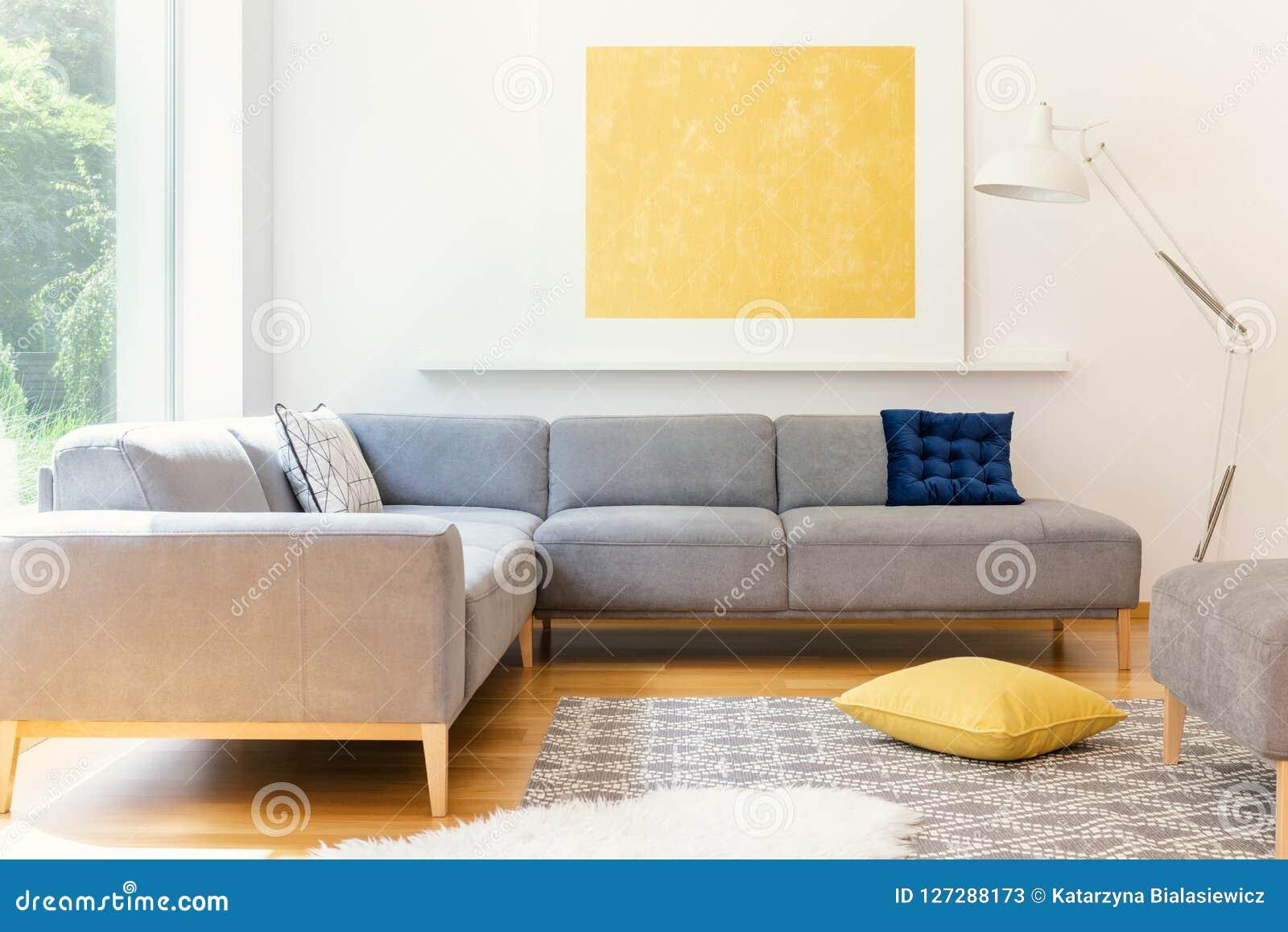 Une affiche minimaliste et jaune et un blanc, un lampadaire industriel dans un intérieur ensoleillé de salon avec une couverture
