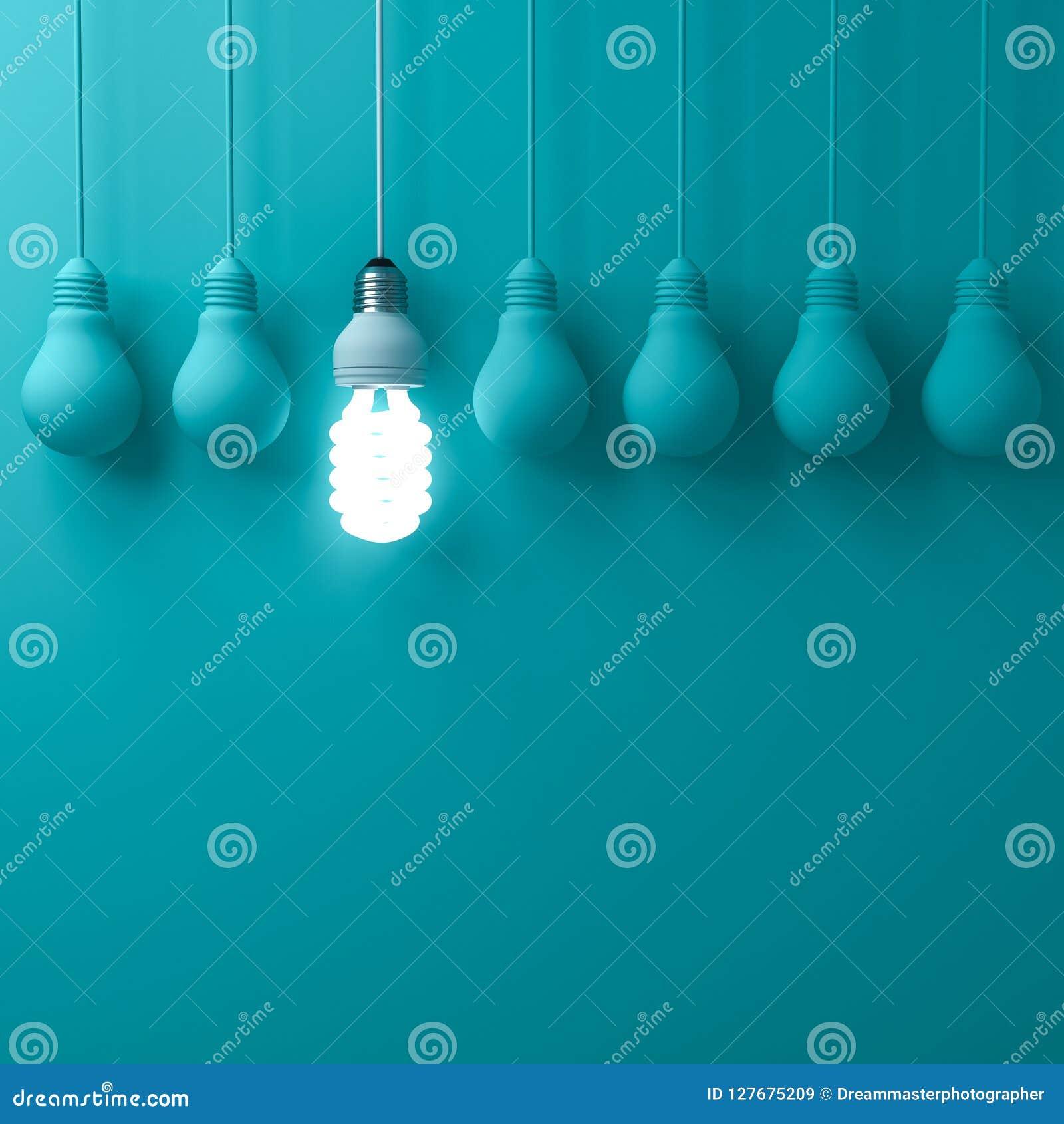 Une ampoule économiseuse d énergie accrochante d eco rougeoyant et se tenant des ampoules incandescentes non allumées sur la coul