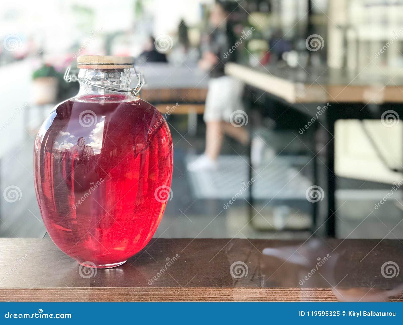 Une banque en verre de grand beau trois-litre d un jambon, jus, breuvage magique, une boisson avec rougeoyer liquide avec un couv