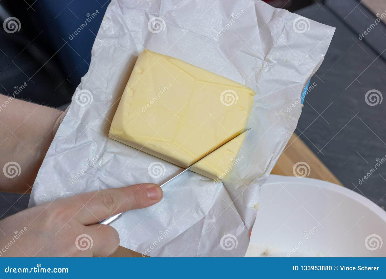 Une barre de beurre sur un conseil en bois avec un couteau