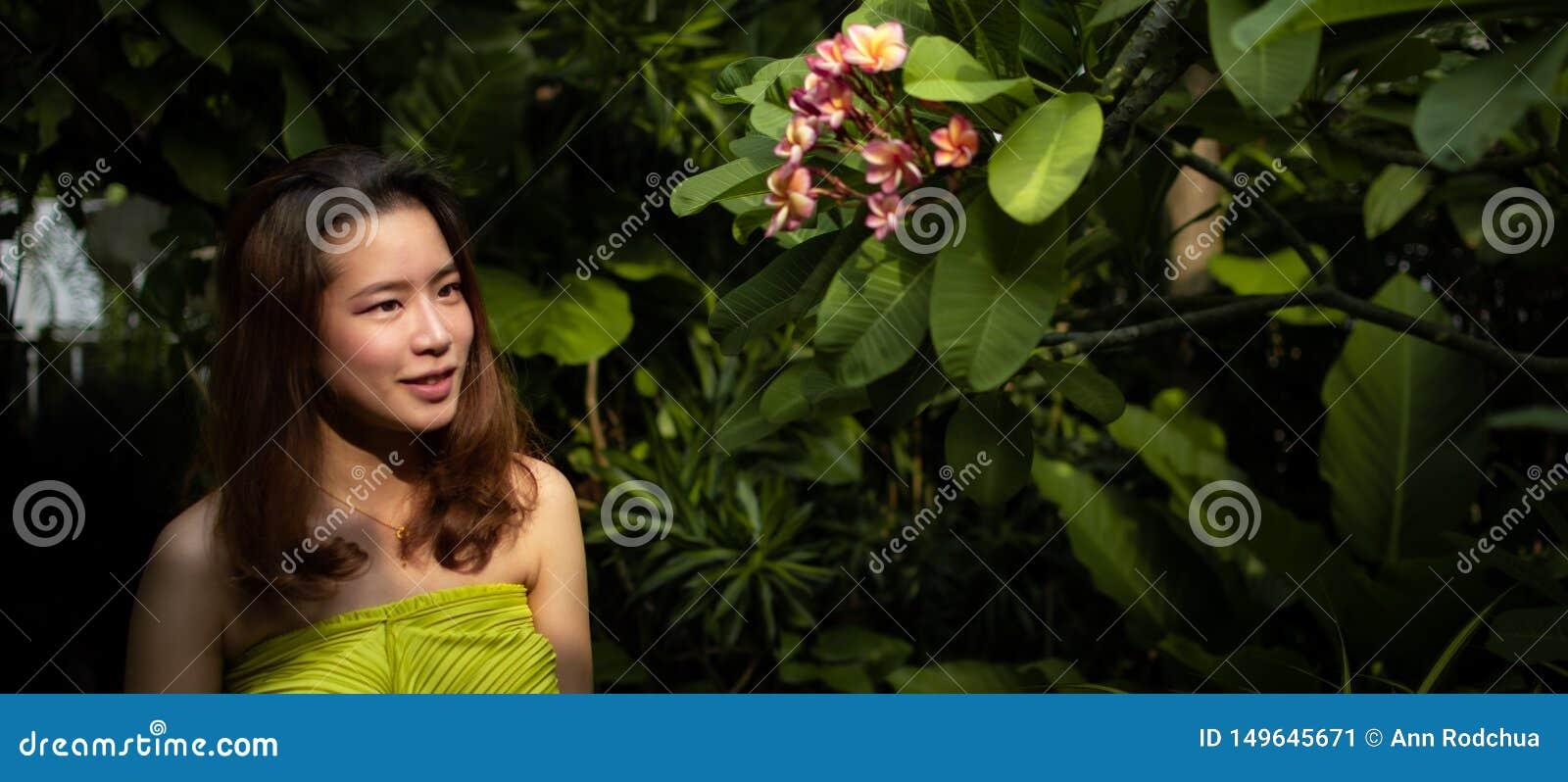 Une belle femme asiatique regarde les fleurs roses dans le jardin