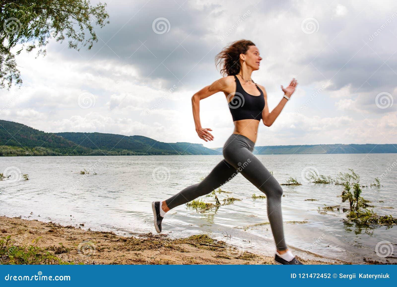Une belle femme sportive courant sur le rivage d un lac dans les sports