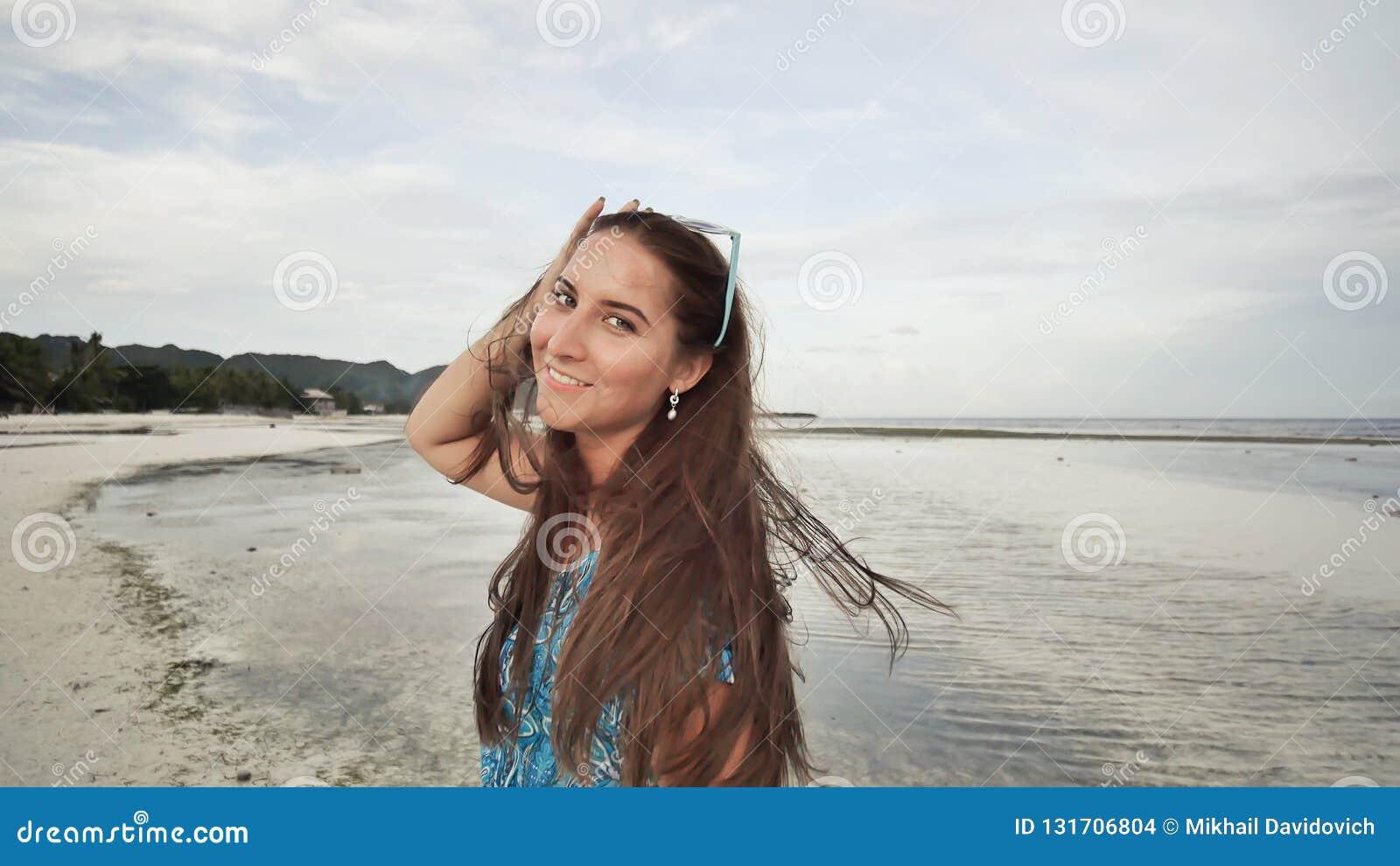 Une belle fille avec de longs cheveux dans une longue robe bleue flâne le long de la plage Fille posant sur l appareil-photo sur