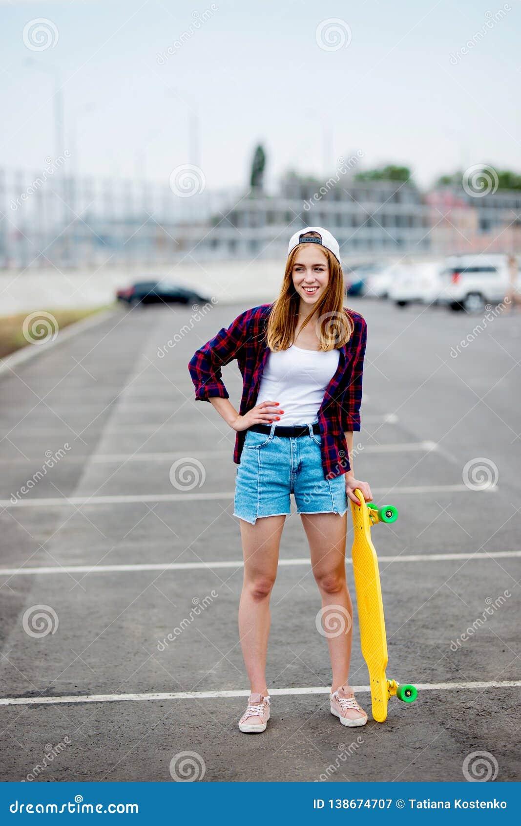 Une belle fille blonde portant les caleçons à carreaux de chemise, de chapeau et de denim se tient sur le parking avec un longboa