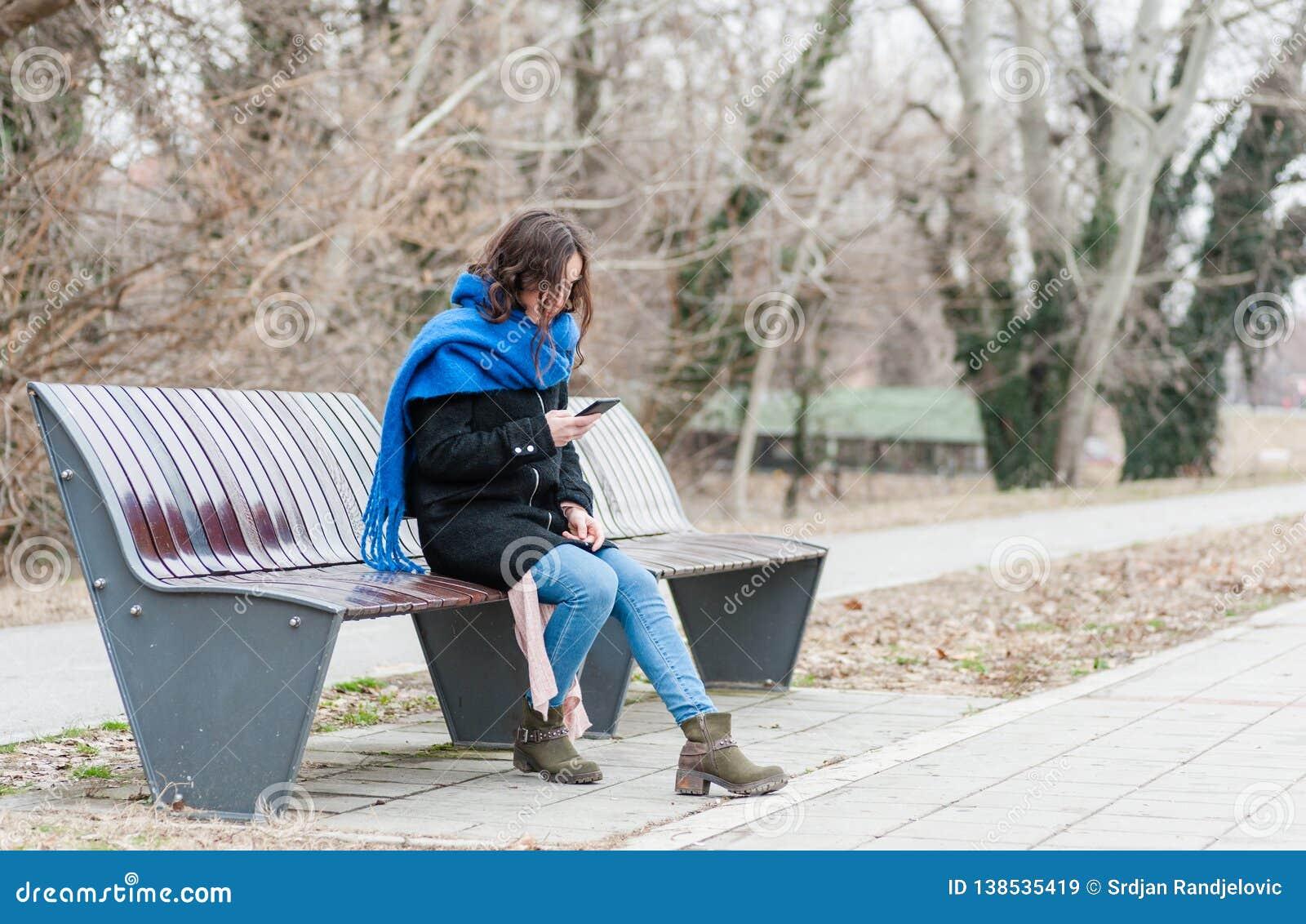 Une belle fille seule seul s asseyant et déprimée sur le banc dans le sentiment de parc abandonné et trahi de son ami W