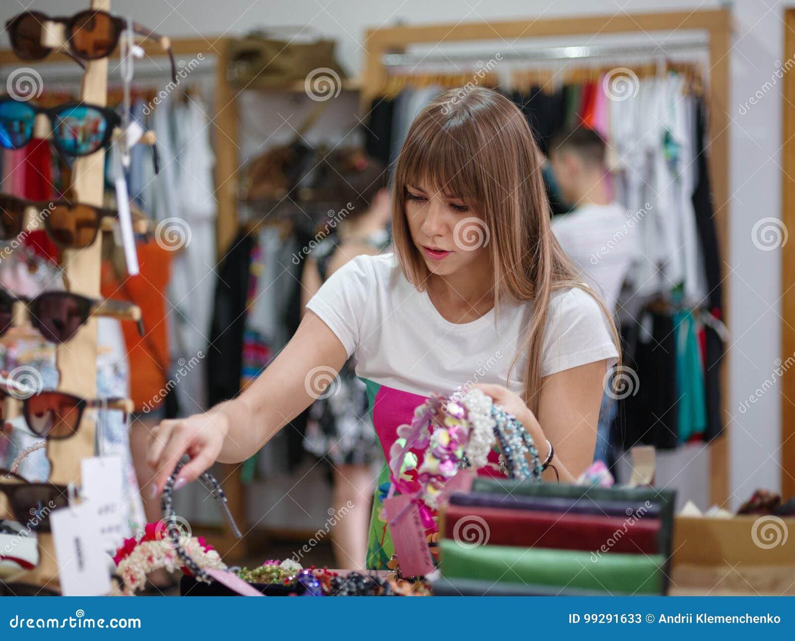 Une belle jeune femme choisissant la bande de cheveux dans une boutique, beaux accessoires pour des femmes sur un fond clair brou