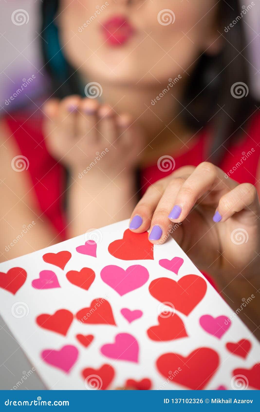 Une belle jeune femme prend une carte avec des coeurs avec une déclaration de l amour Jour du `s de Valentine