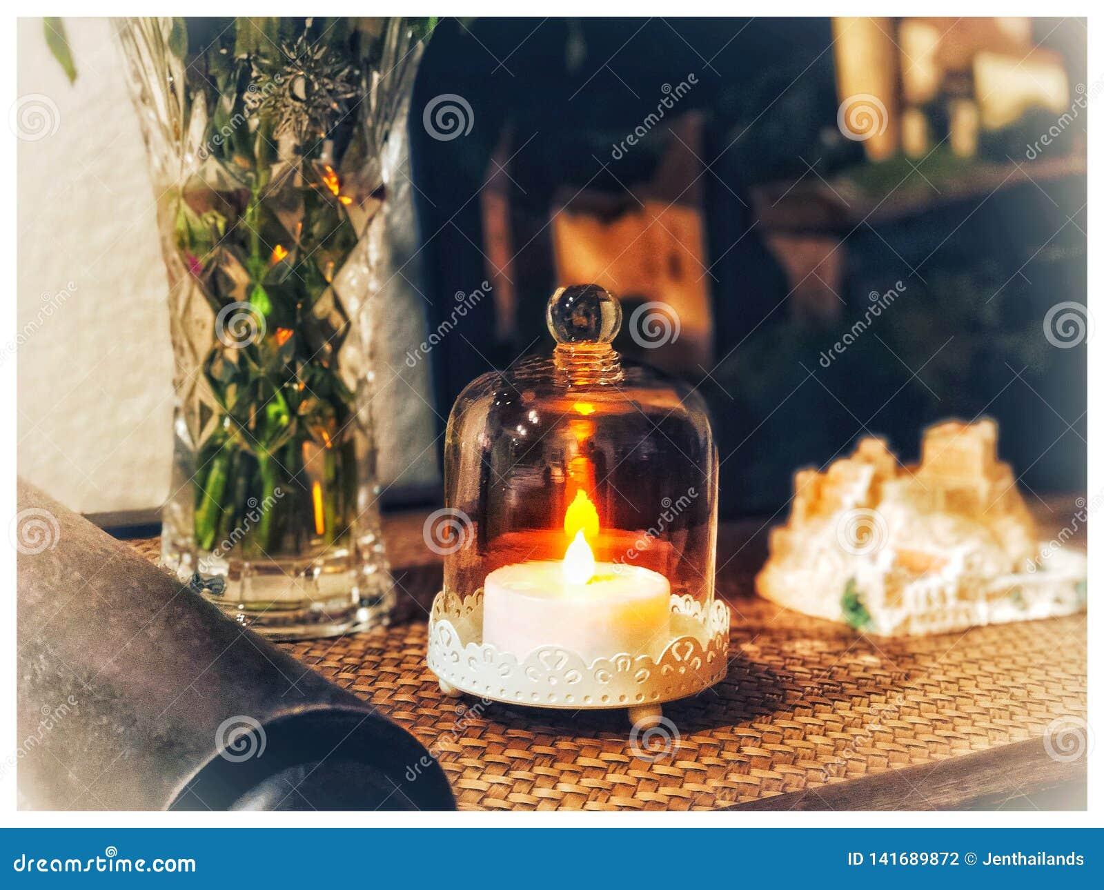 Une bougie électrique brûlant sous un verre sur la table