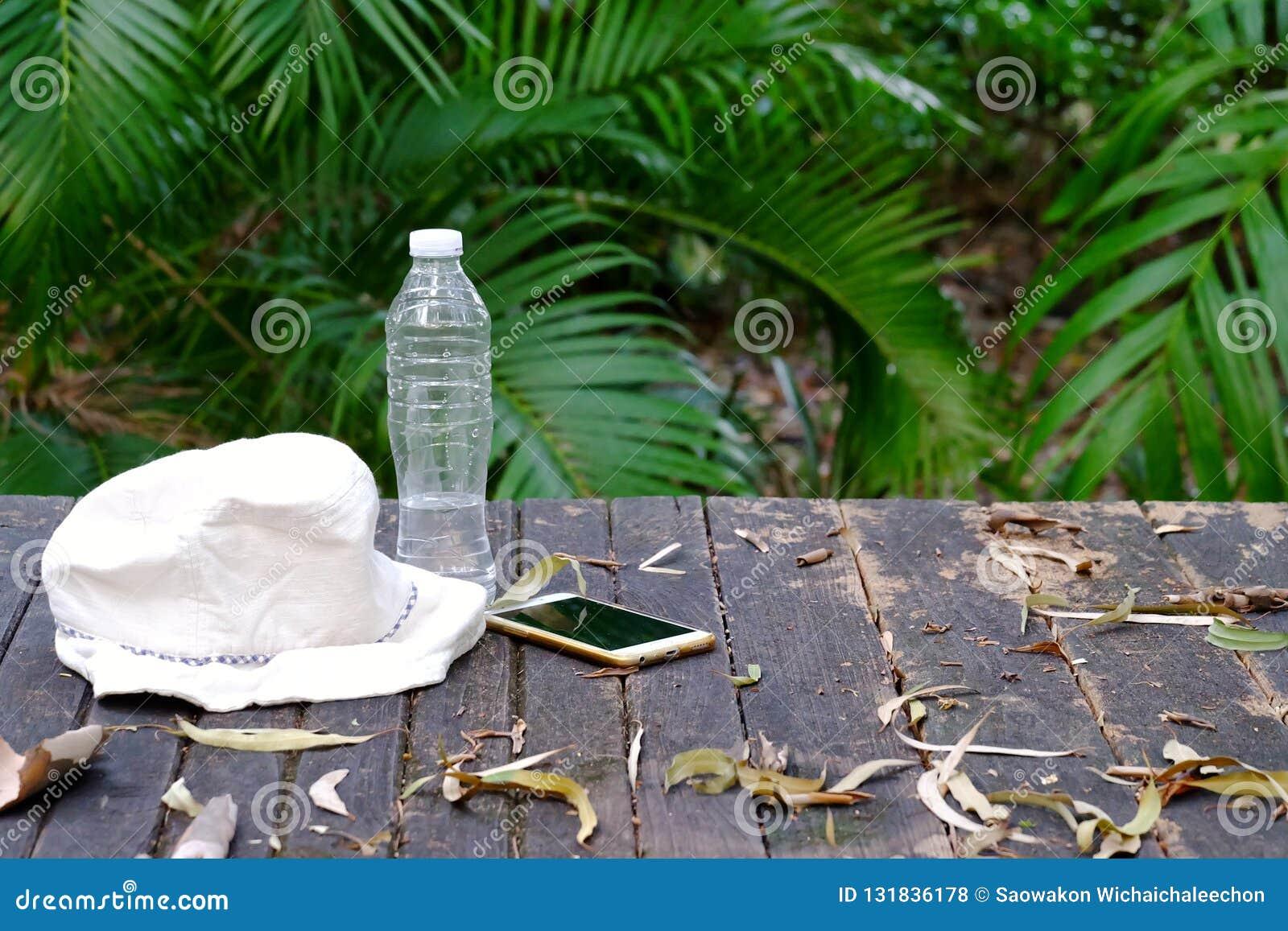 Une bouteille d eau potable, de chapeau et de téléphone portable sur la table en bois avec le fond vert de nature