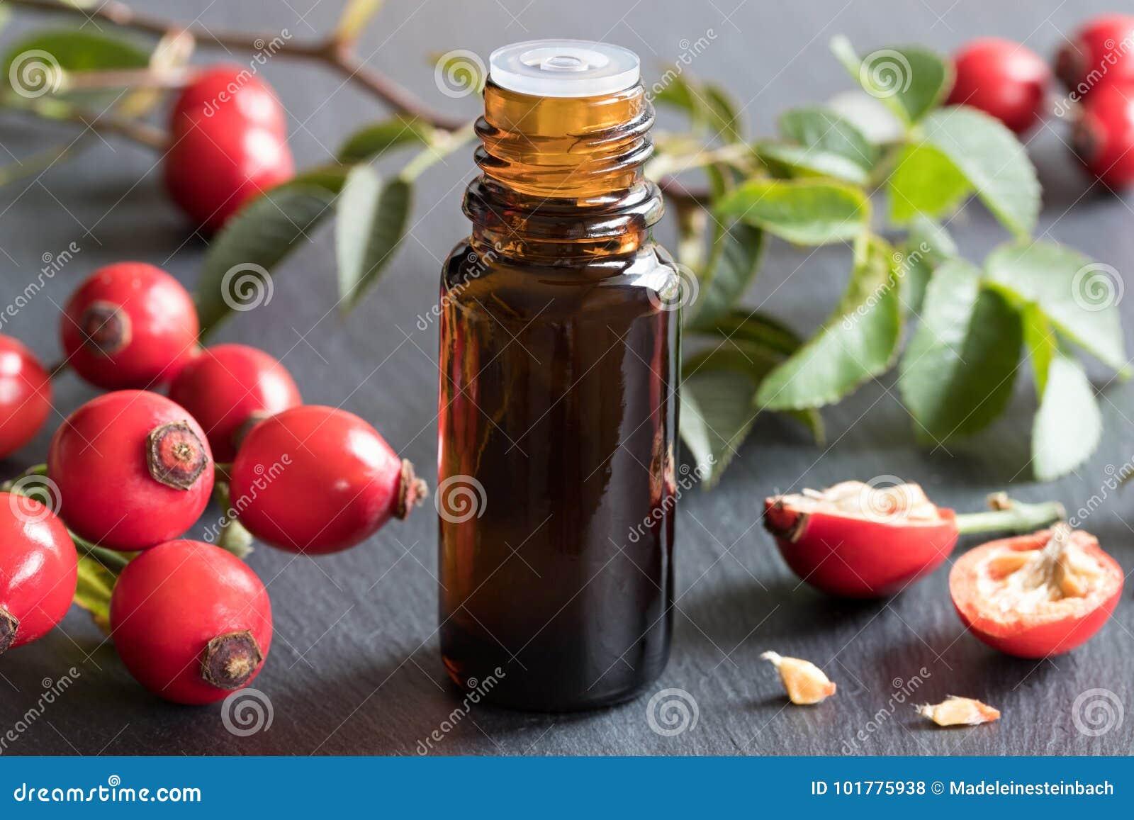 Une bouteille d huile de graines de hanche rose sur un fond gris