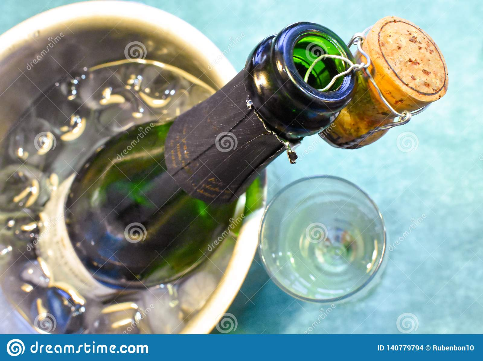 Une bouteille de champagne dans un seau froid avec de l eau la glace et, la participation de liège de la bouche décorant la scène