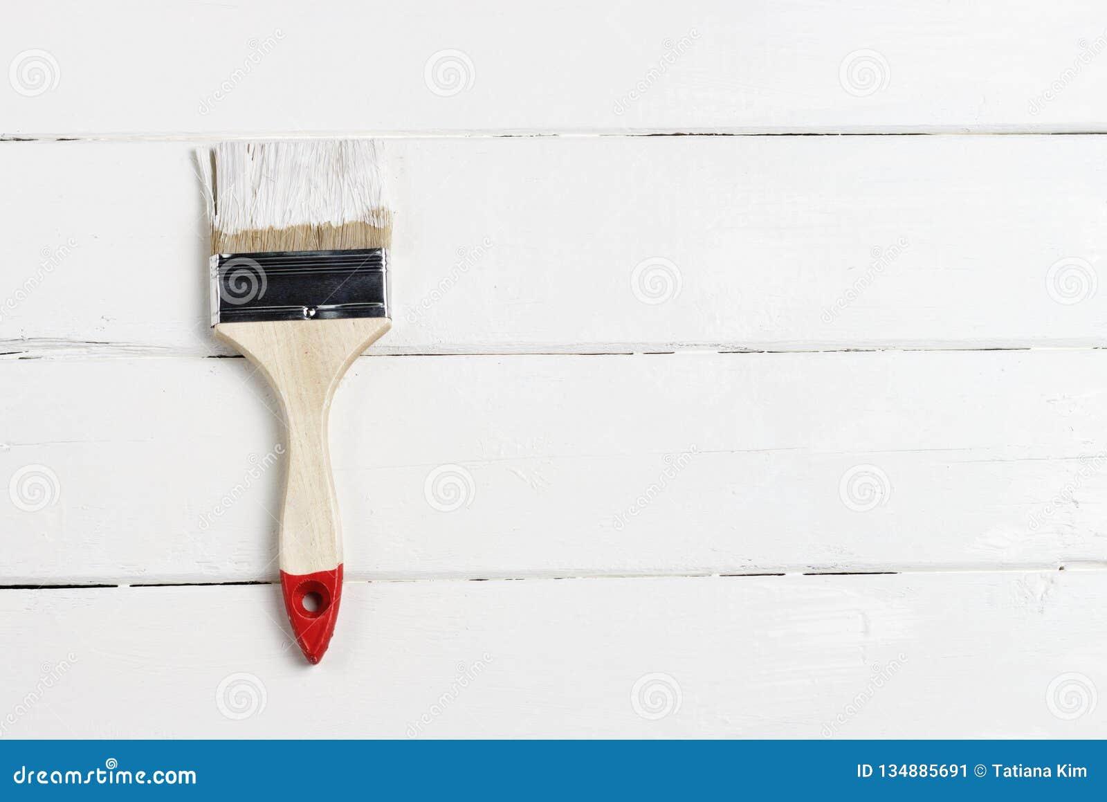 Une brosse avec la peinture blanche sur un fond peint en bois, l espace de copie, vue supérieure
