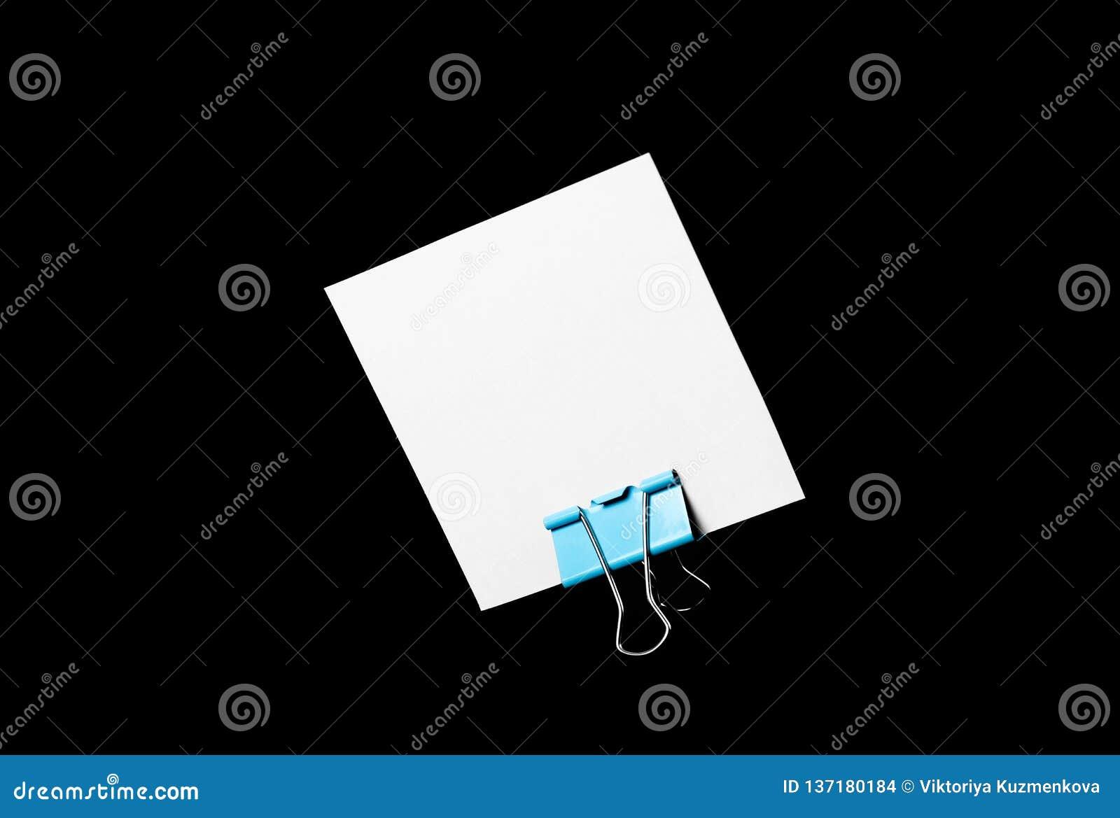 Une carte de visite professionnelle de visite blanche vide se tient sur une agrafe de papeterie Fin vers le haut D isolement sur