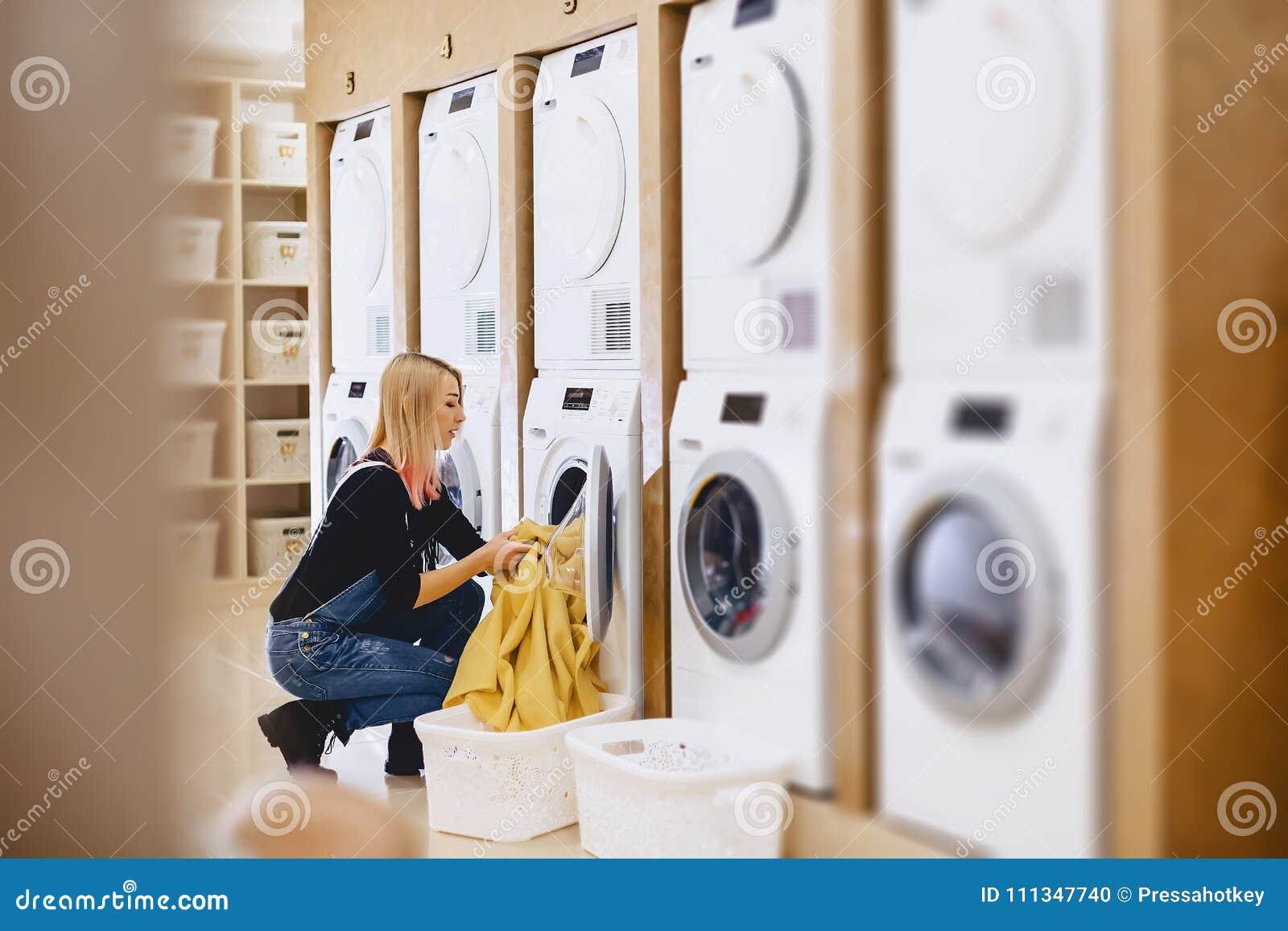 Une charge de femme les feuilles dans la blanchisserie à laver et sécher