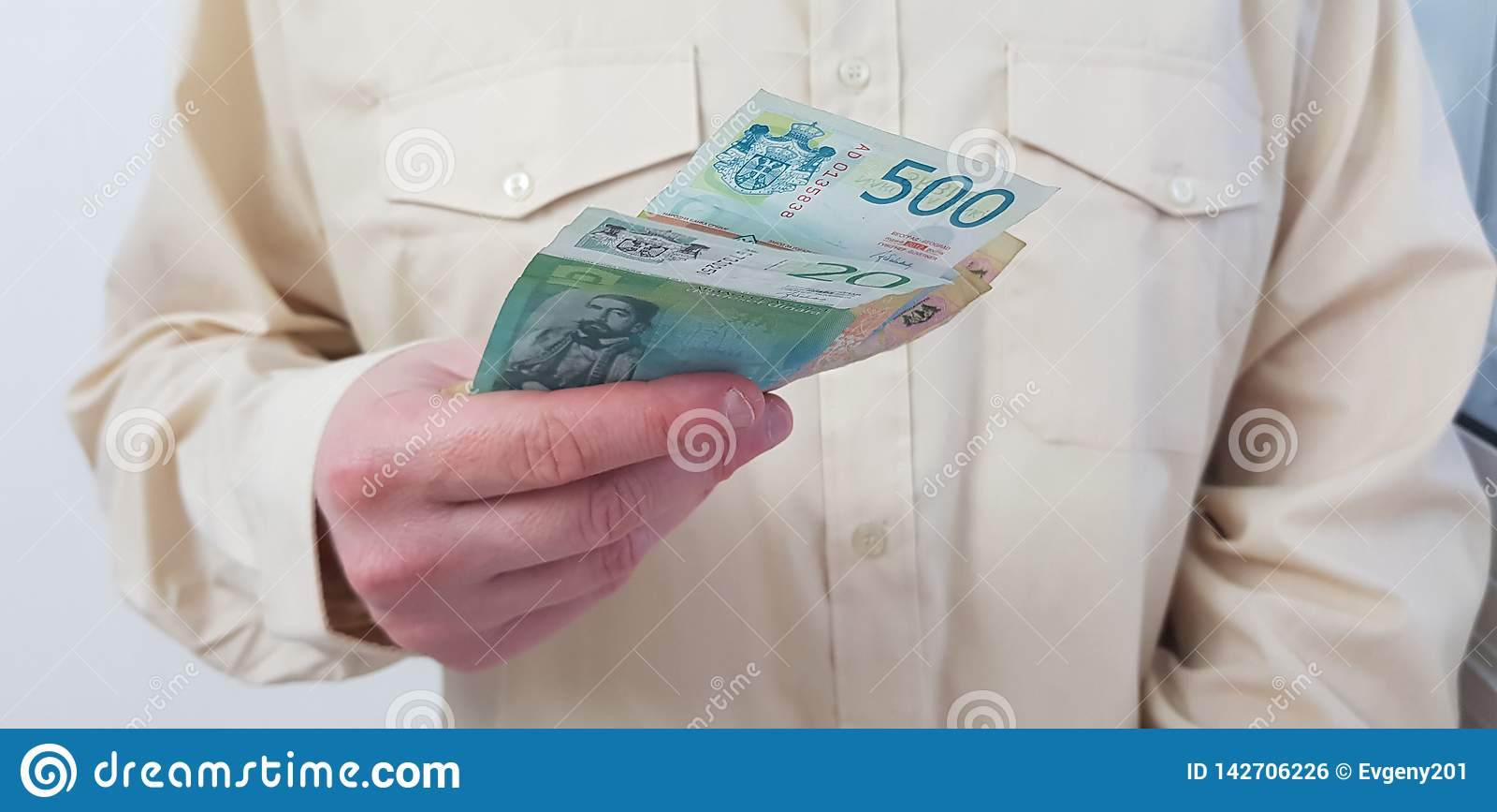 Une chemise officielle de couleur claire de port de position d homme se tient en sa monnaie fiduciaire serbe de main