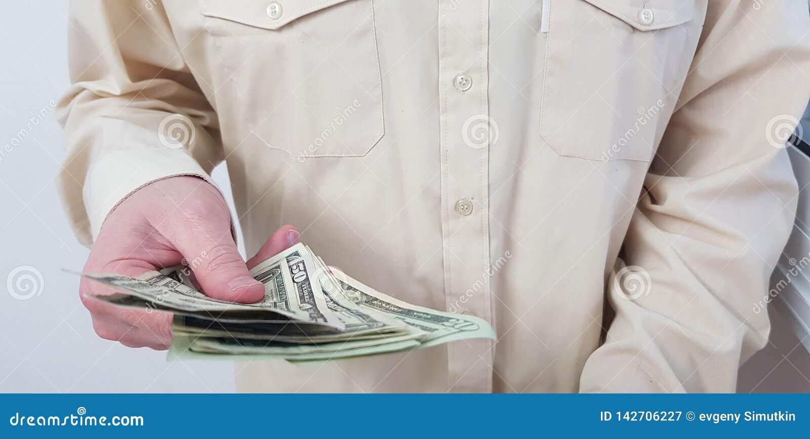 Une chemise officielle de couleur claire de port de position d homme se tient en son dollar américain de main