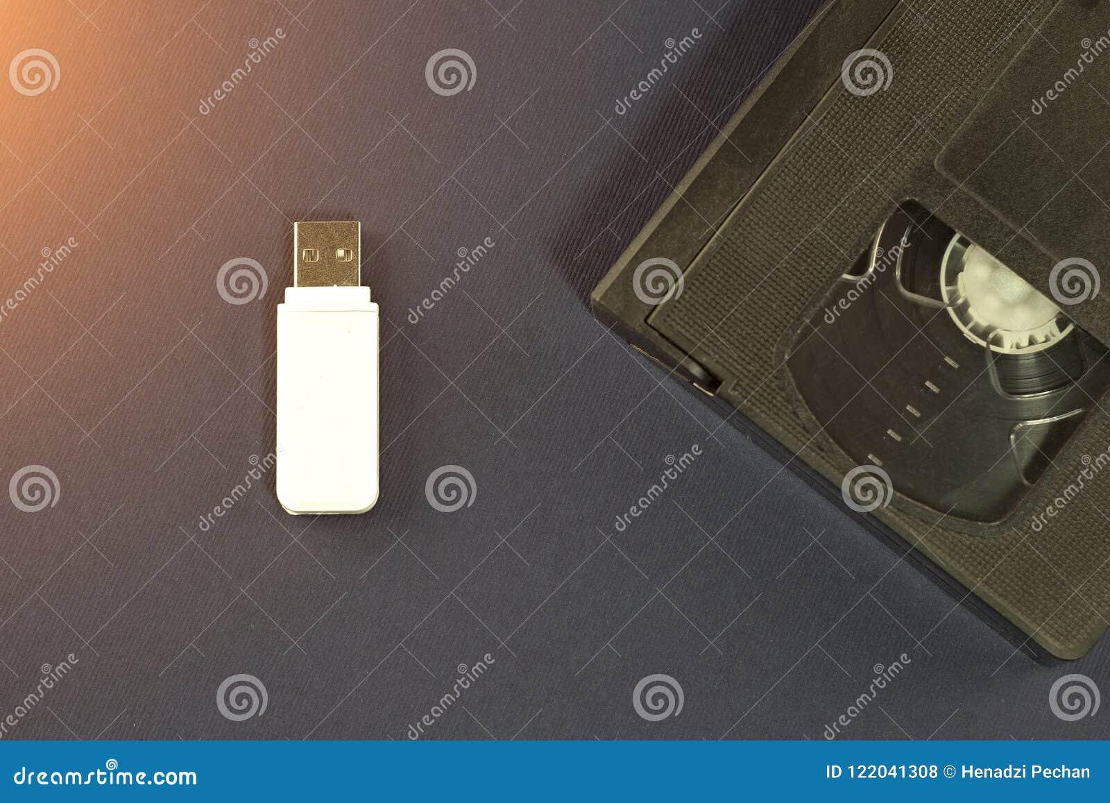 Une commande instantanée blanche sur un fond bleu et une cassette vidéo, usb