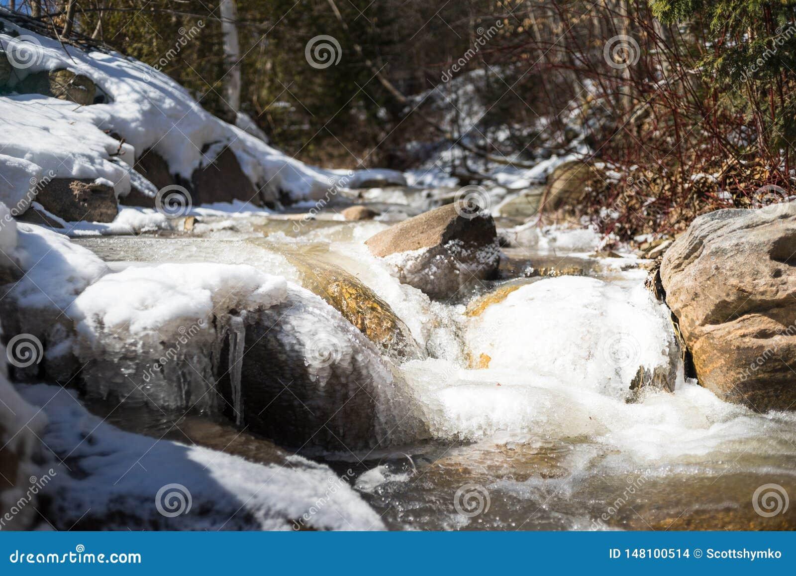 Une crique court la glace pass?e et la neige a couvert des rochers