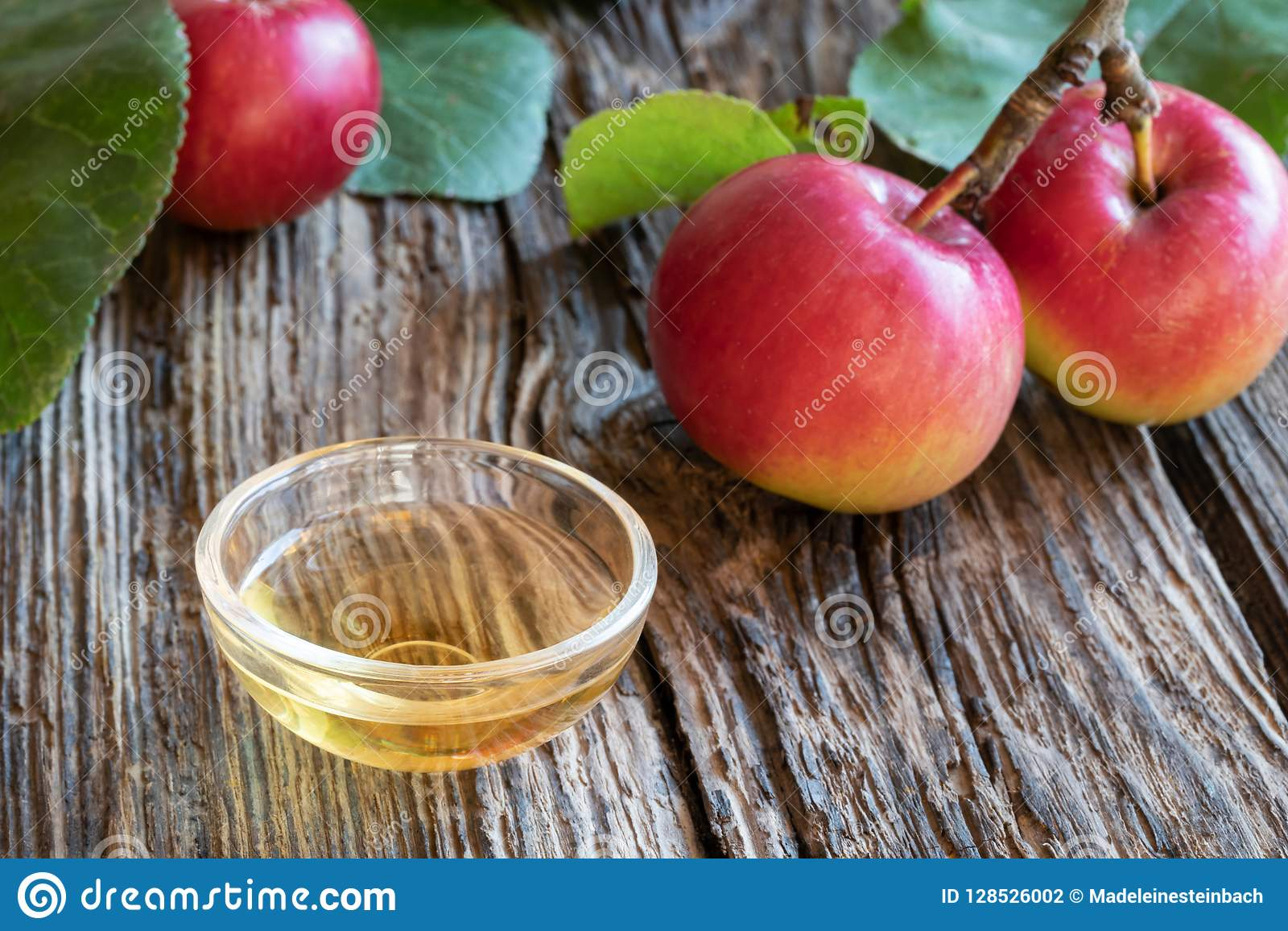 Une cuvette de vinaigre de cidre de pomme avec les pommes fraîches