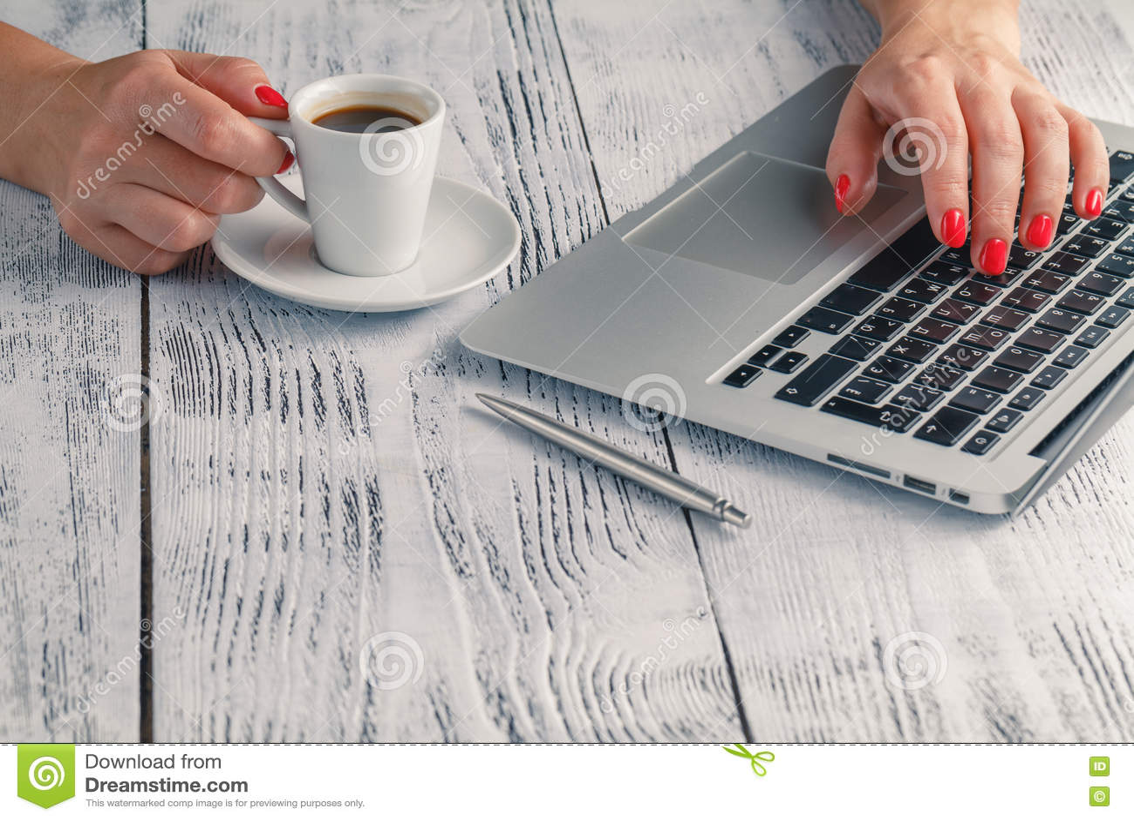 Une dame tient le café dans sa main au bureau de PC