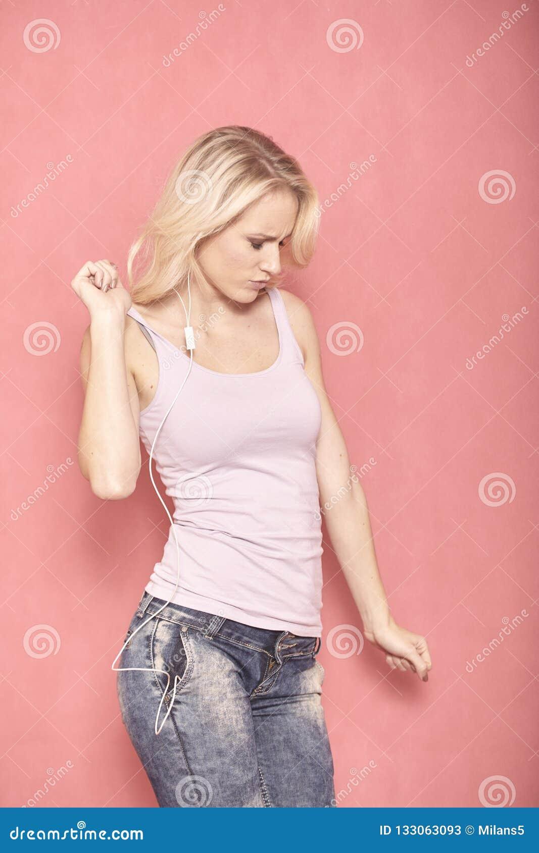 Une danse de jeune femme en musique, ?coutant sur des ?couteurs, l appr?ciant vraiment avec ses yeux s est ferm?e