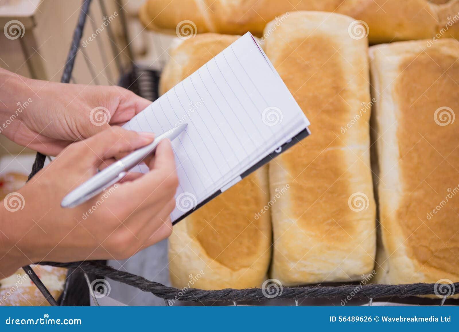 Une femme écrivant une liste d épicerie au-dessus de pain de pain