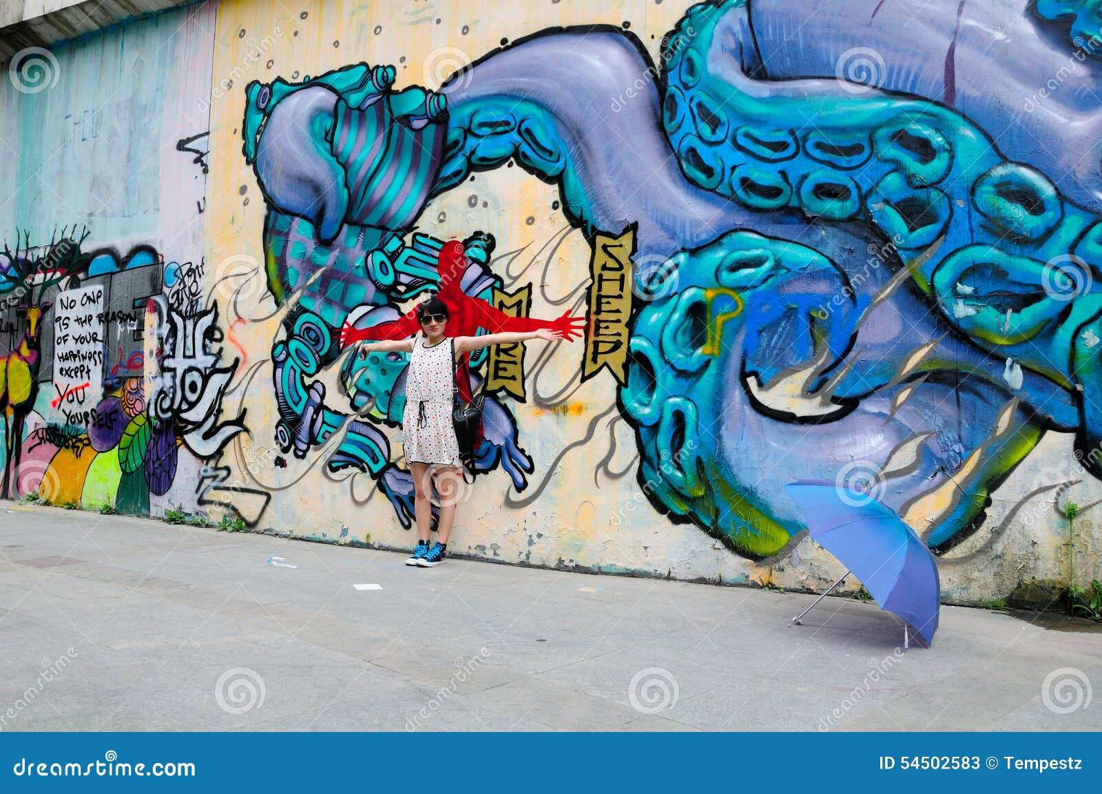 Une femme asiatique posant près du graffiti