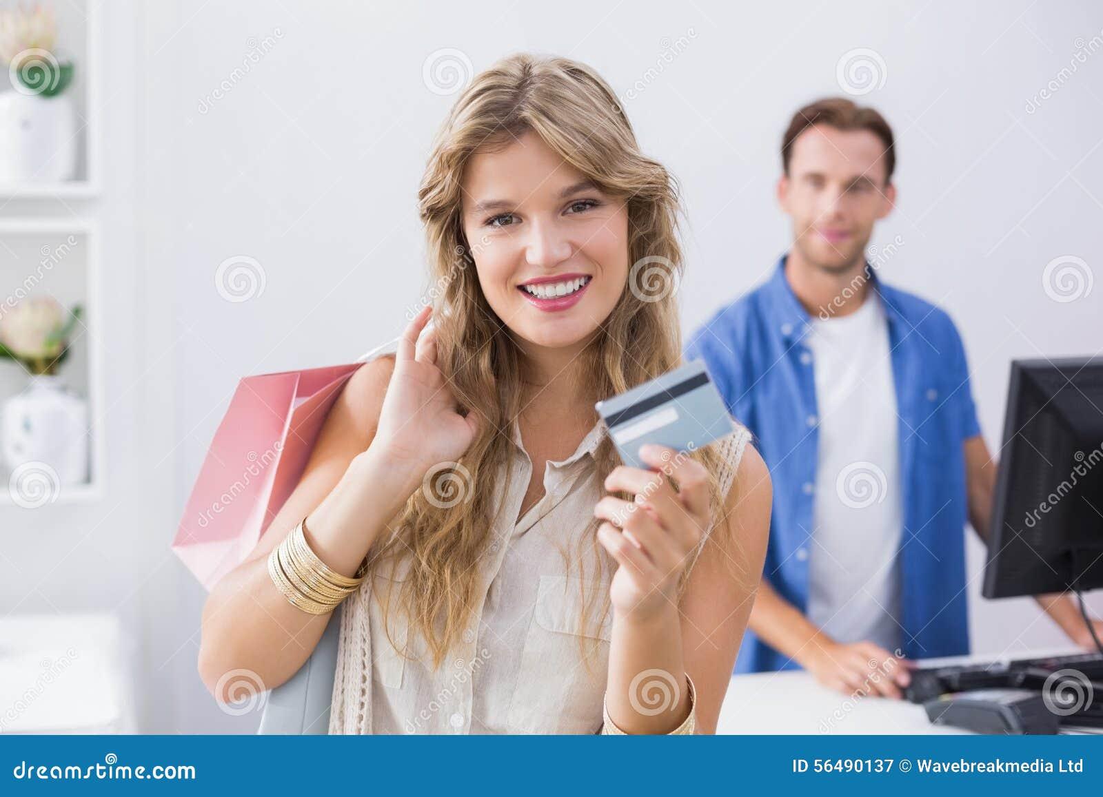 Une femme assez blonde montrant ses cartes de crédit