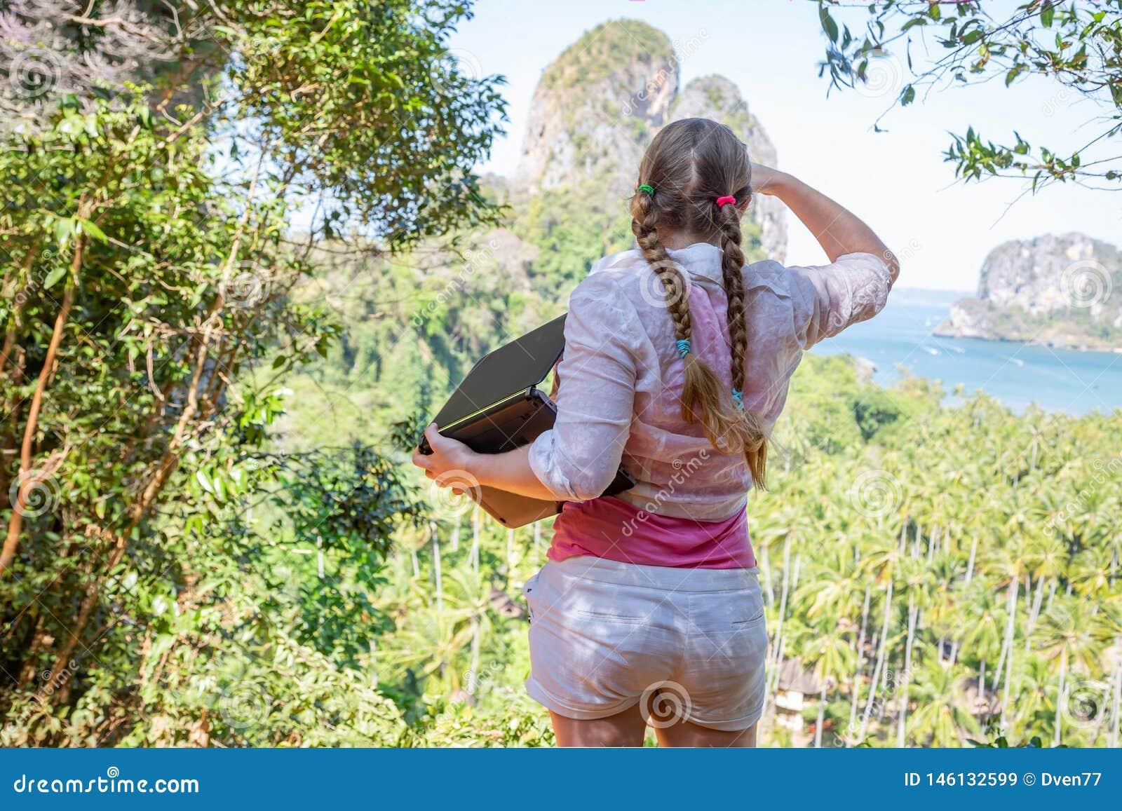 Une femme avec un ordinateur portable en haut des examinations de montagne la distance Le travailleur d industrie du tourisme pré