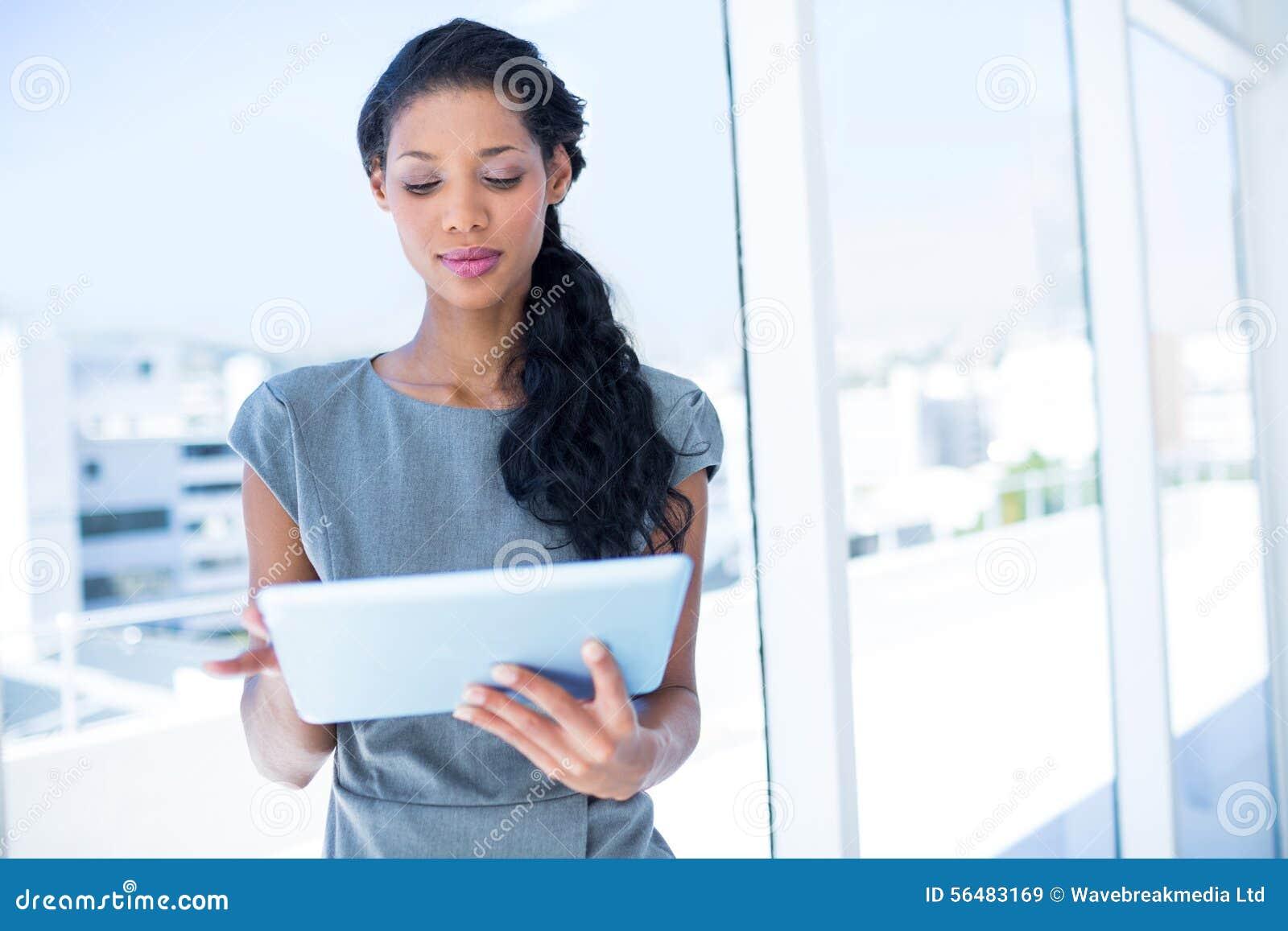 Une femme d affaires focalisée à l aide du comprimé numérique