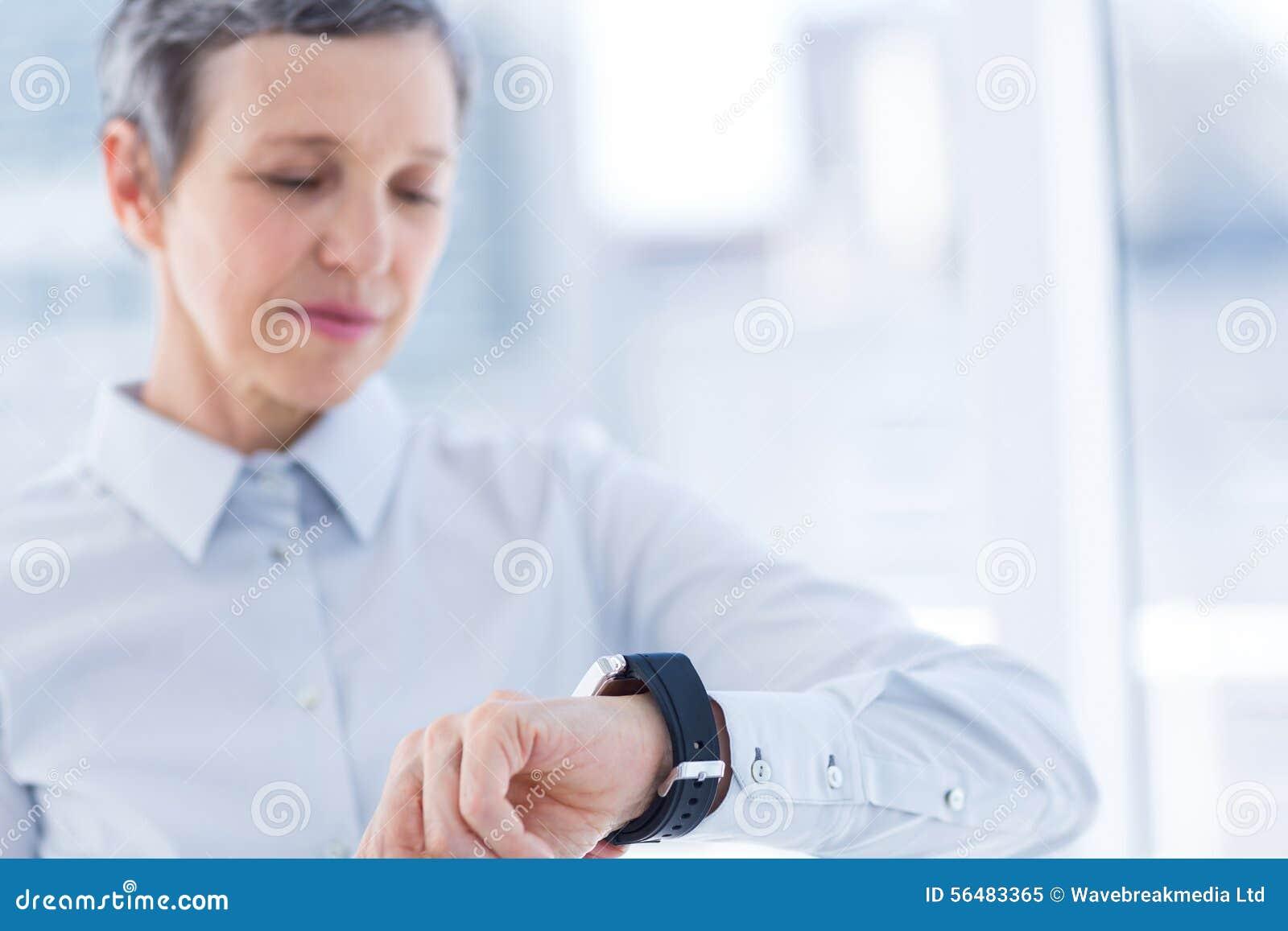 Une femme d affaires regardant son smartwatch
