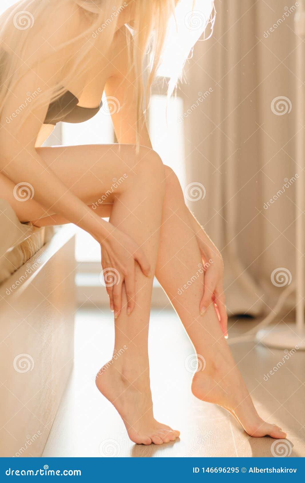 Une femme dans les sous-vêtements avec les jambes convenables parfaites se reposant sur le lit dans la chambre ensoleillée