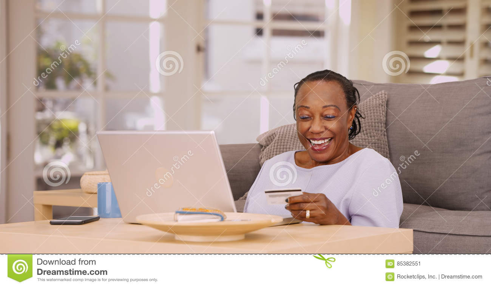 Une femme de couleur plus âgée lui paye des factures sur son ordinateur portable