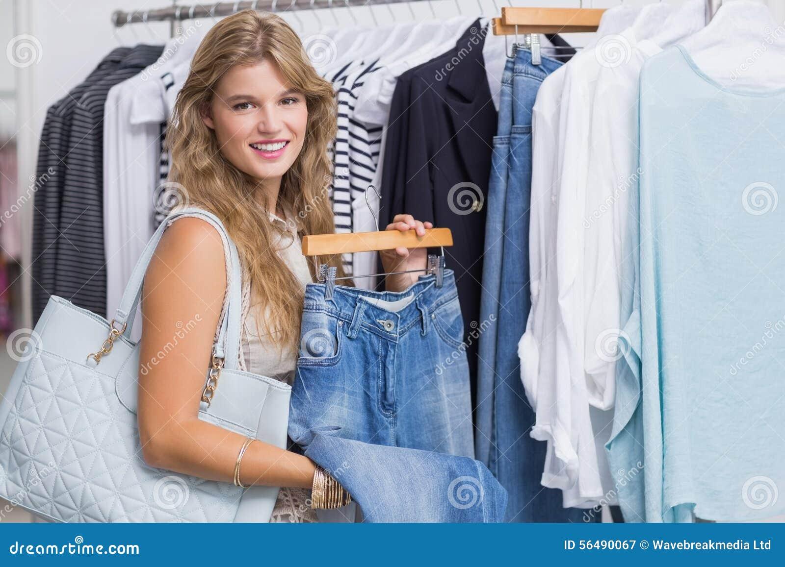 Une femme de sourire heureuse choisissant quelques vêtements