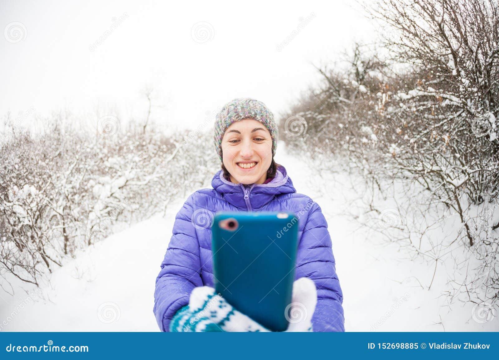 Une femme fait une photo ? un t?l?phone portable dans la for?t d hiver
