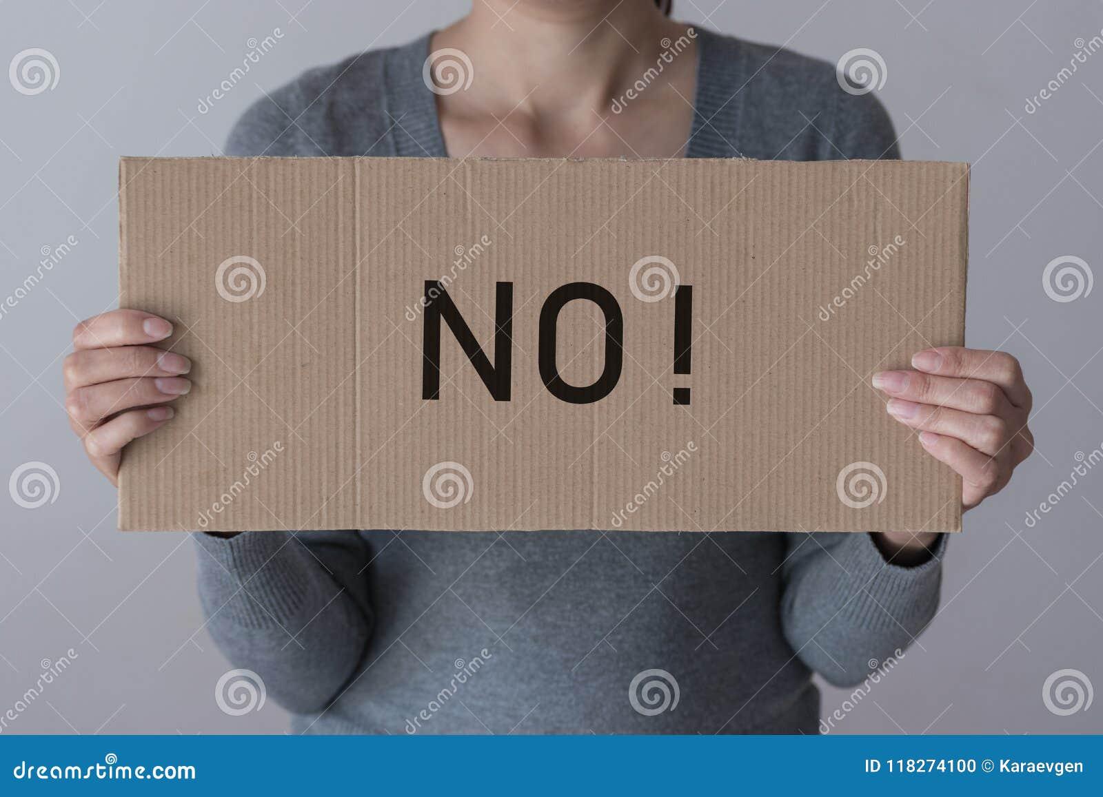 Une femme juge une bannière avec l inscription AUCUNE